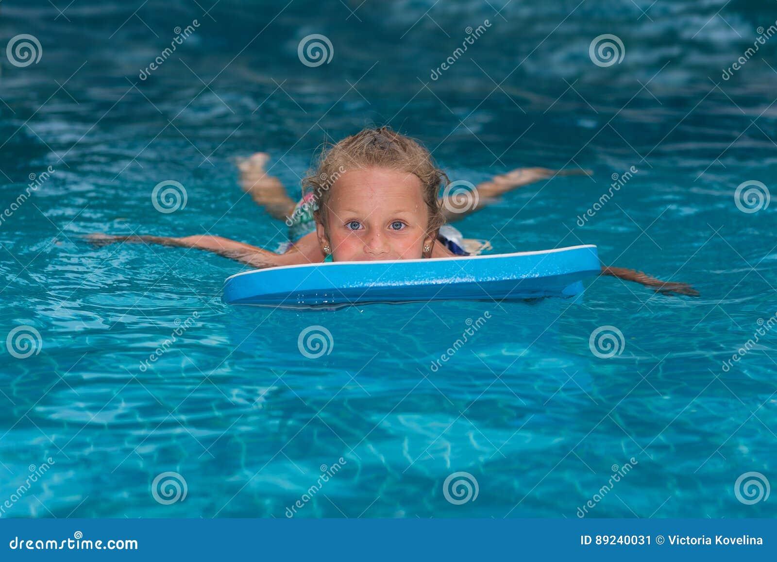 Mała dziewczynka uczenie pływać w dużym sporta basenie Pływacka szkoła dla małych dzieci Zdrowy dzieciak cieszy się aktywnego sty