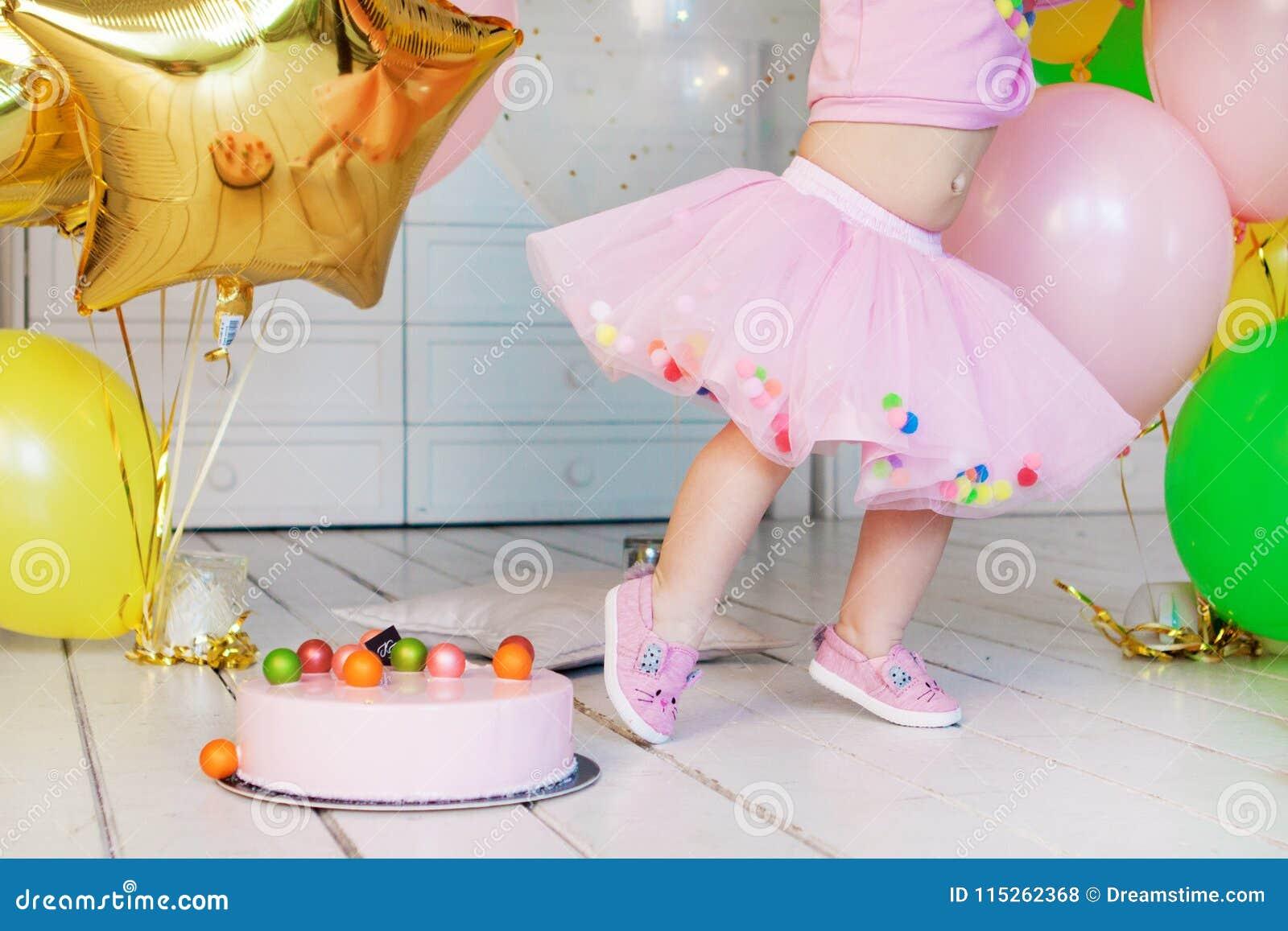 Mała dziewczynka w różowej puszystej spódnicie Różowy mousse tort z kolorowymi piłkami na białej drewnianej podłoga