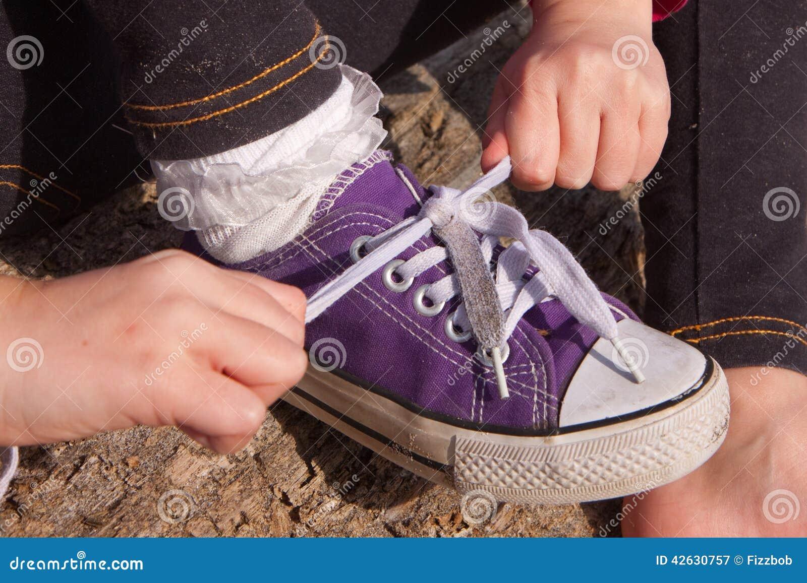 Mała dziewczynka wiąże shoelaces
