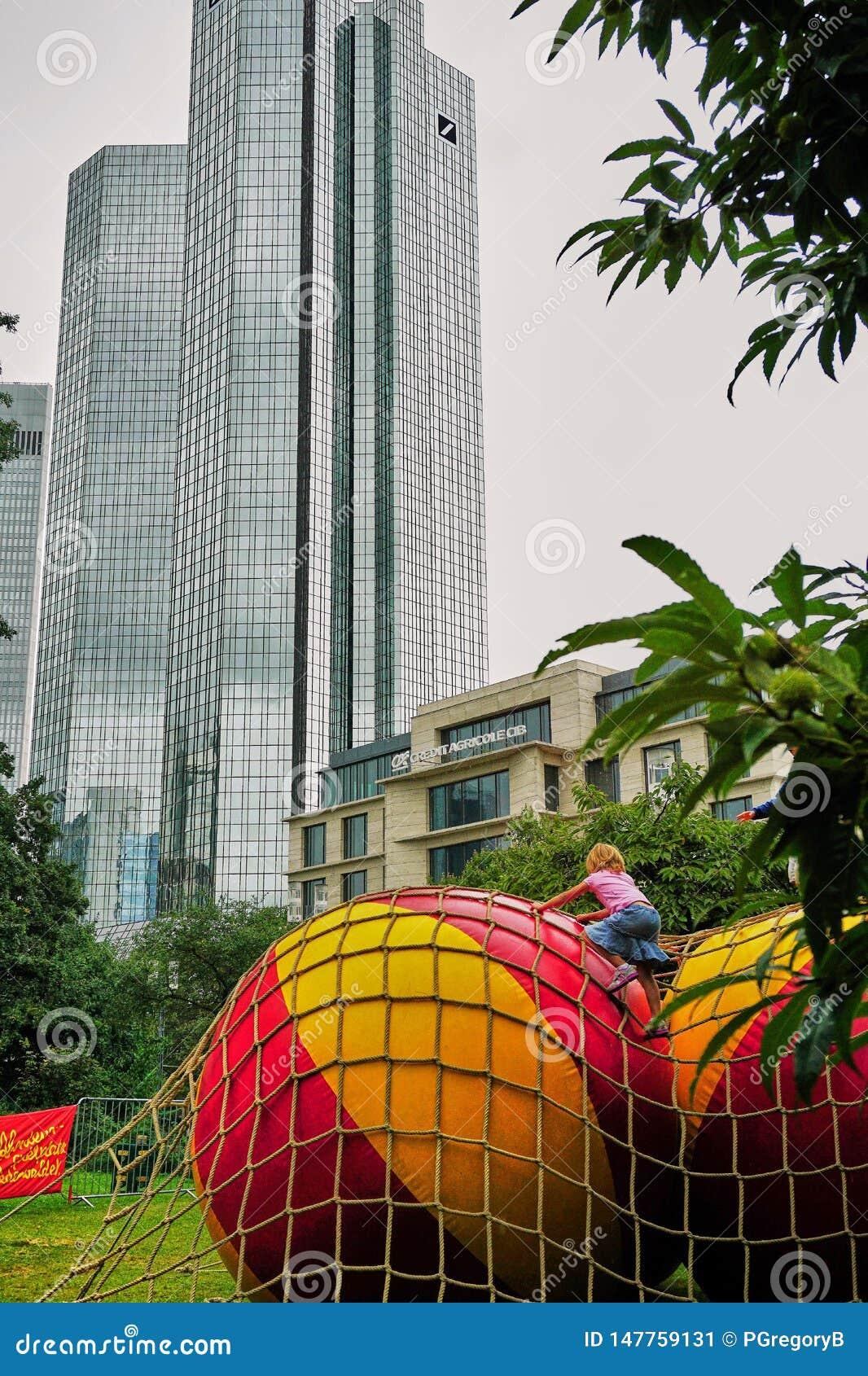 Mała dziewczynka wspina się ogromne plażowe piłki w miastowej dżungli w centrum Frankfurt
