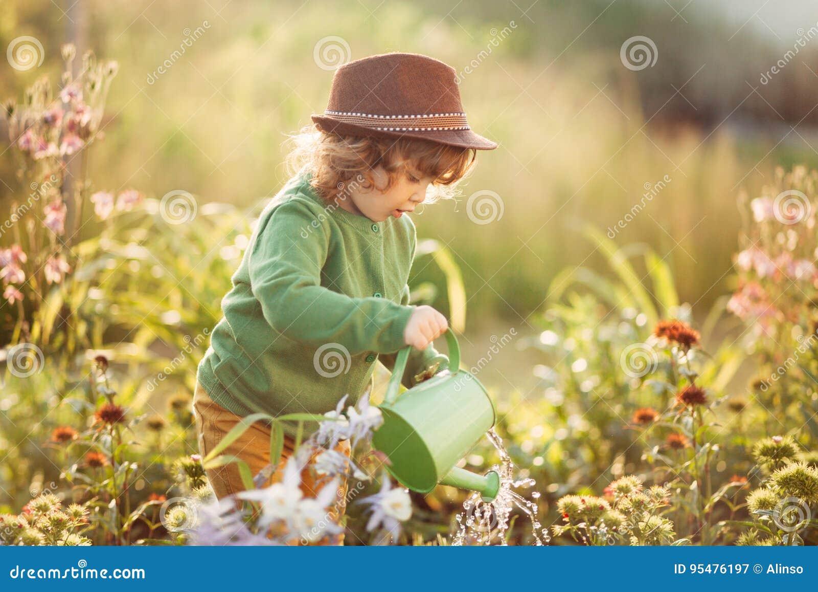 Mała dziewczynka z podlewanie puszką w ogródzie