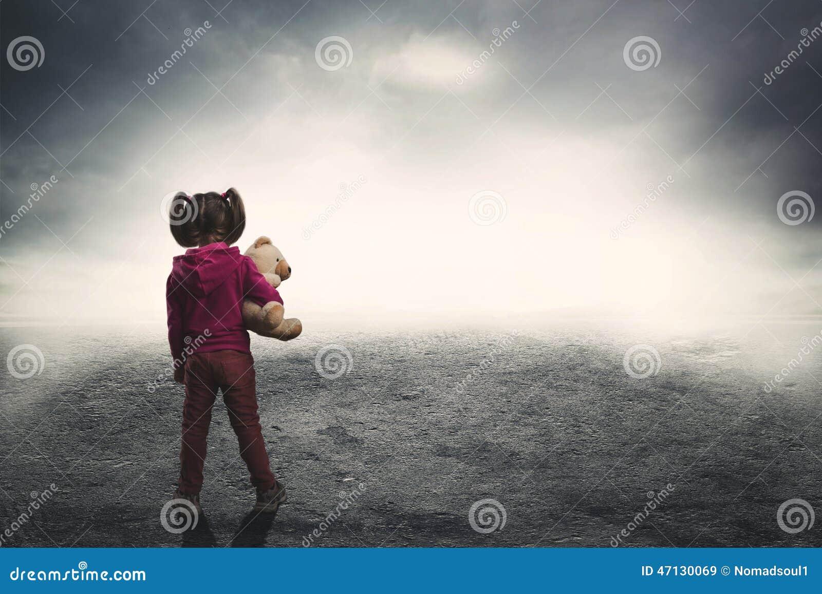 Mała dziewczynka z zabawka niedźwiedziem w ciemności
