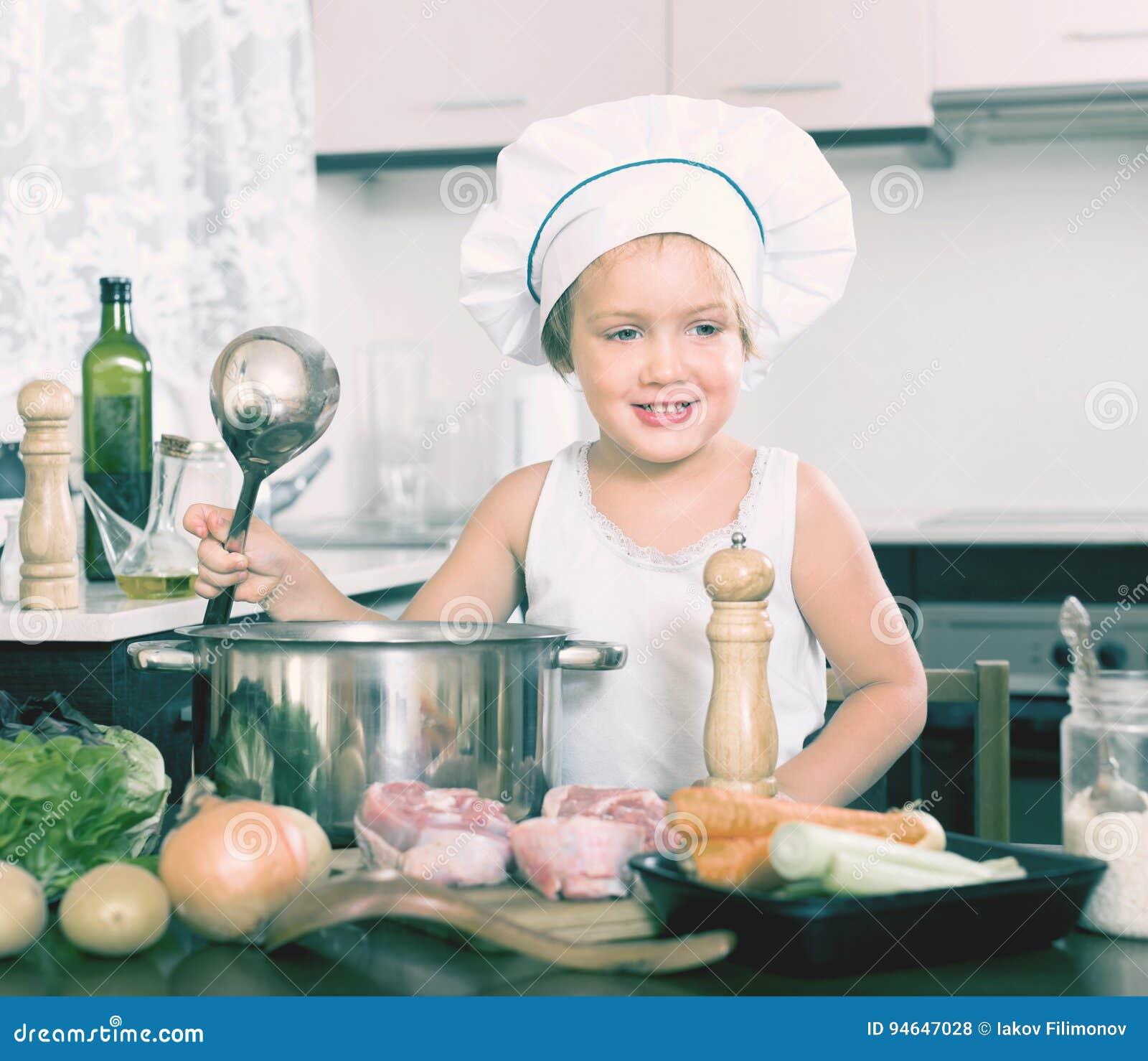 Mała dziewczyny narządzania polewka z warzywami