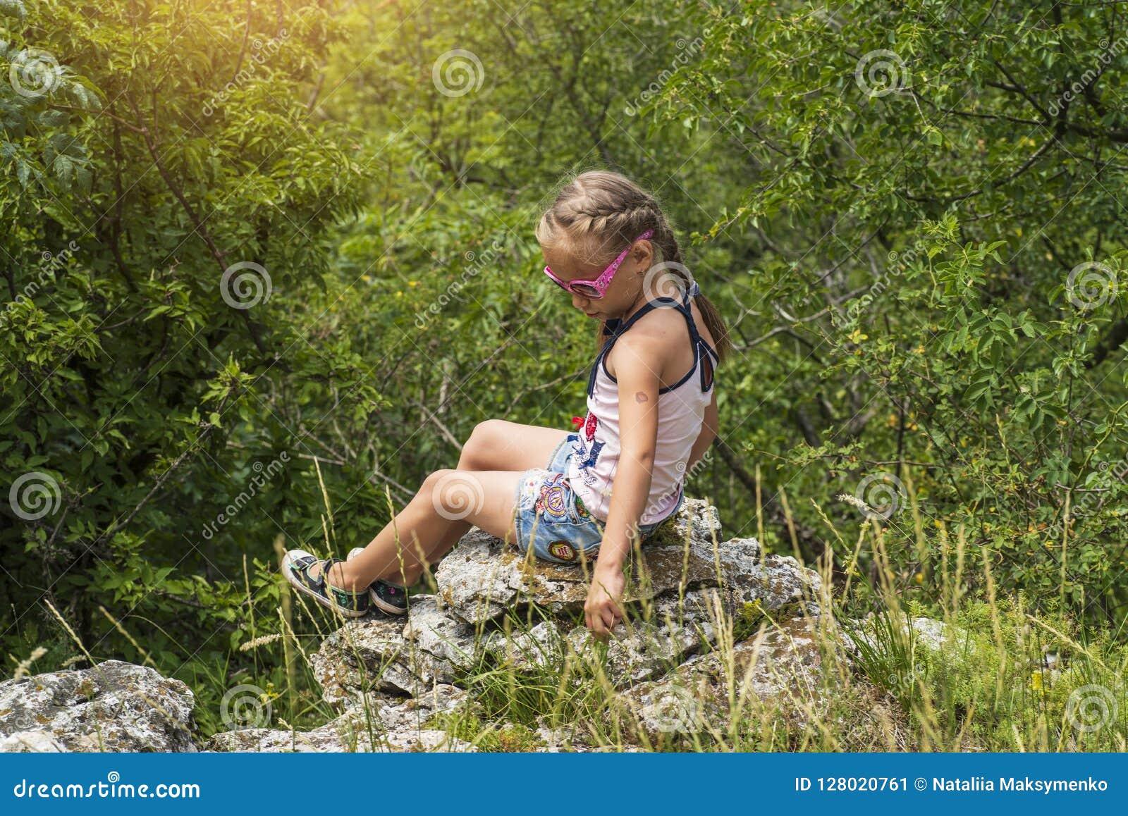 Mała jaskrawa dziewczyna siedzi na krawędzi spojrzeń i góry w odległość na górach