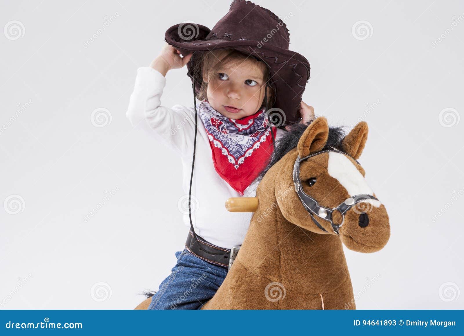 Mała Kaukaska dziewczyna w Cowgirl odzieży Pozuje Na Symbolicznym koniu Przeciw bielowi Trzymać Jej Stetson