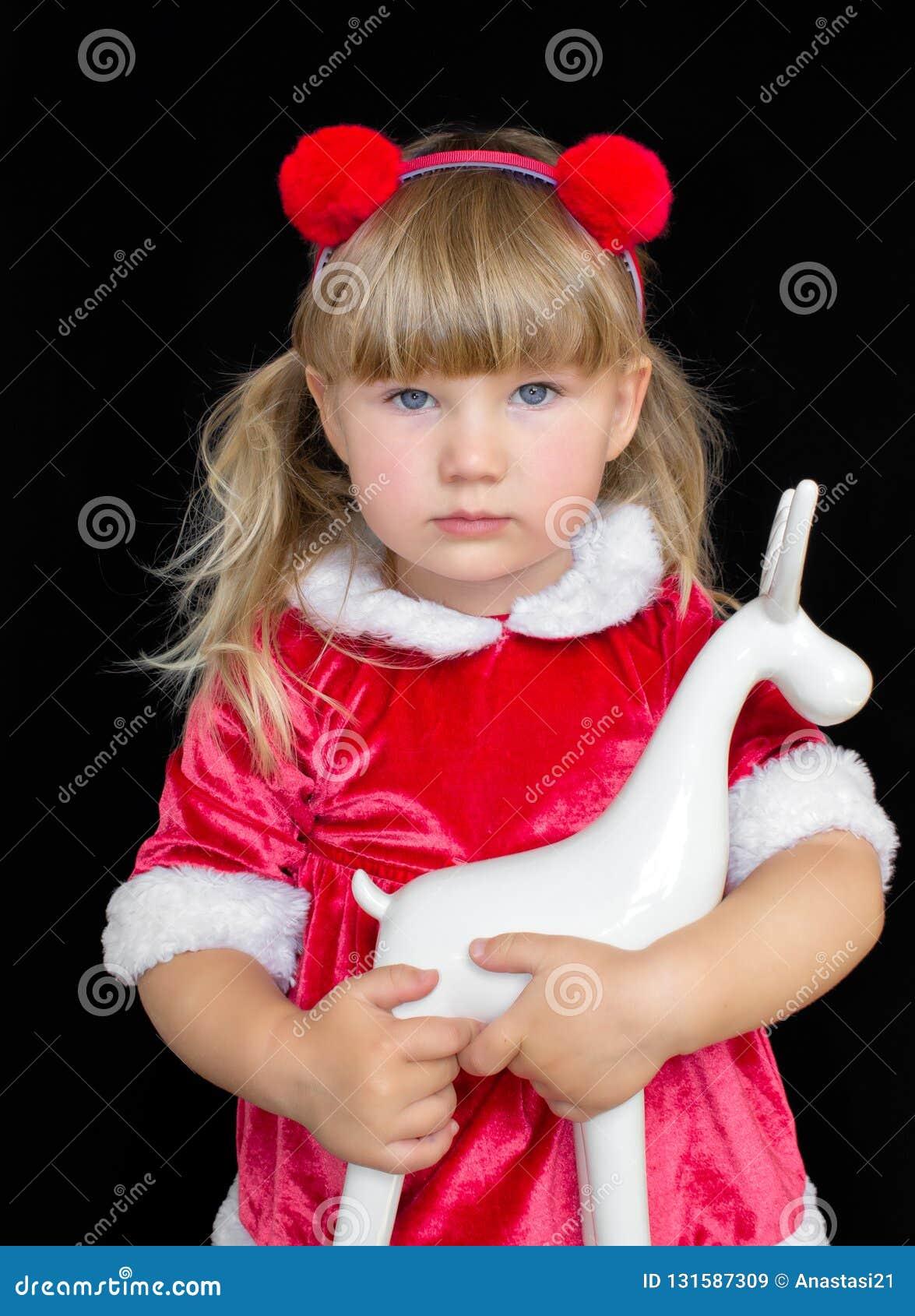Mała piękna dziewczyna w Bożenarodzeniowym Santa kostiumu z futerkowymi piłkami na jej głowie, trzyma rogacza w ruach Pojęcie odś