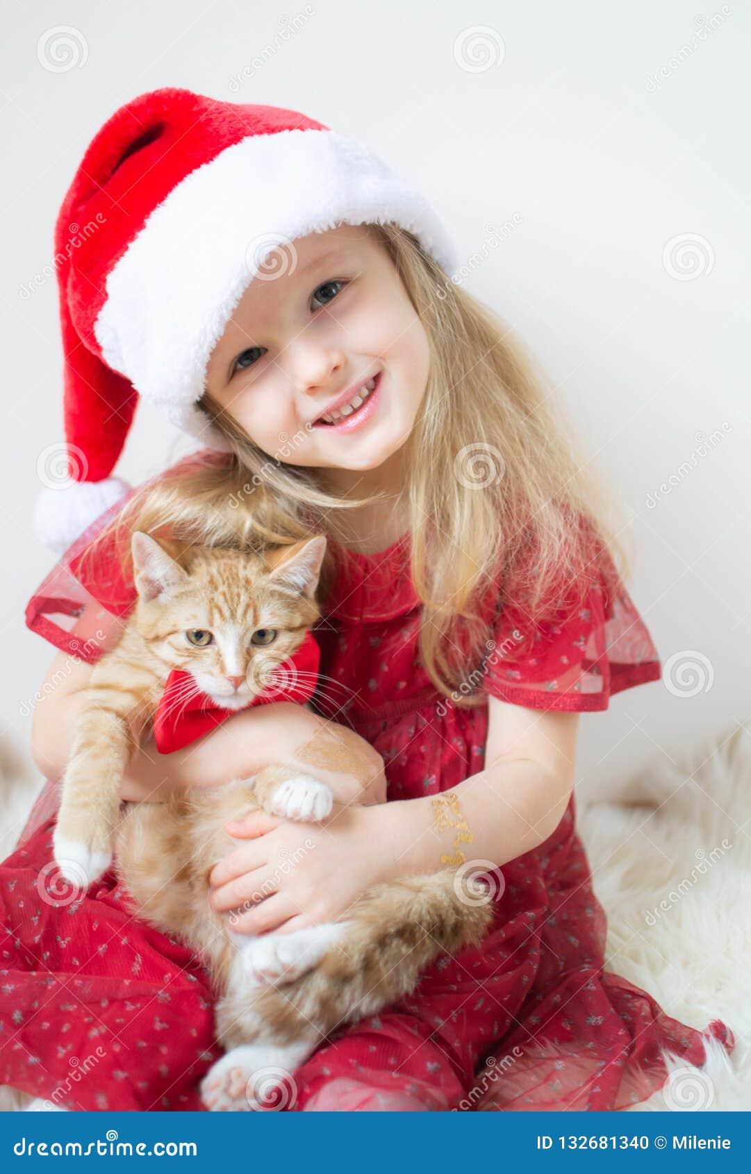 Mała Piękna dziewczyna w Santa Kapeluszowej Czerwonej Partyjnej sukni z Małą Imbirową figlarką Czekać na boże narodzenia i nowego