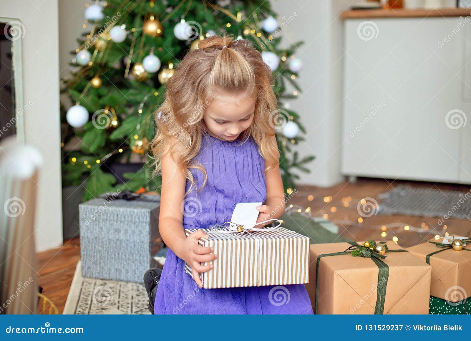 Mała piękna dziewczyna z blond kędzierzawym włosy rozważa jej prezenty przeciw tłu choinka Boże Narodzenia