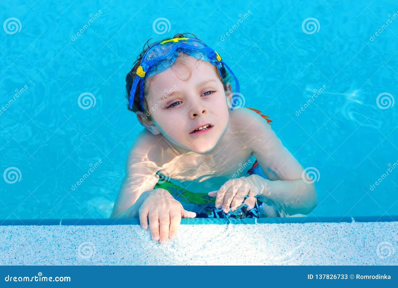 Mała preschool dzieciak chłopiec robi pływaniu turniejowemu sportowi Dzieciak dosięga krawędź basen z pływackimi gogle kochanie