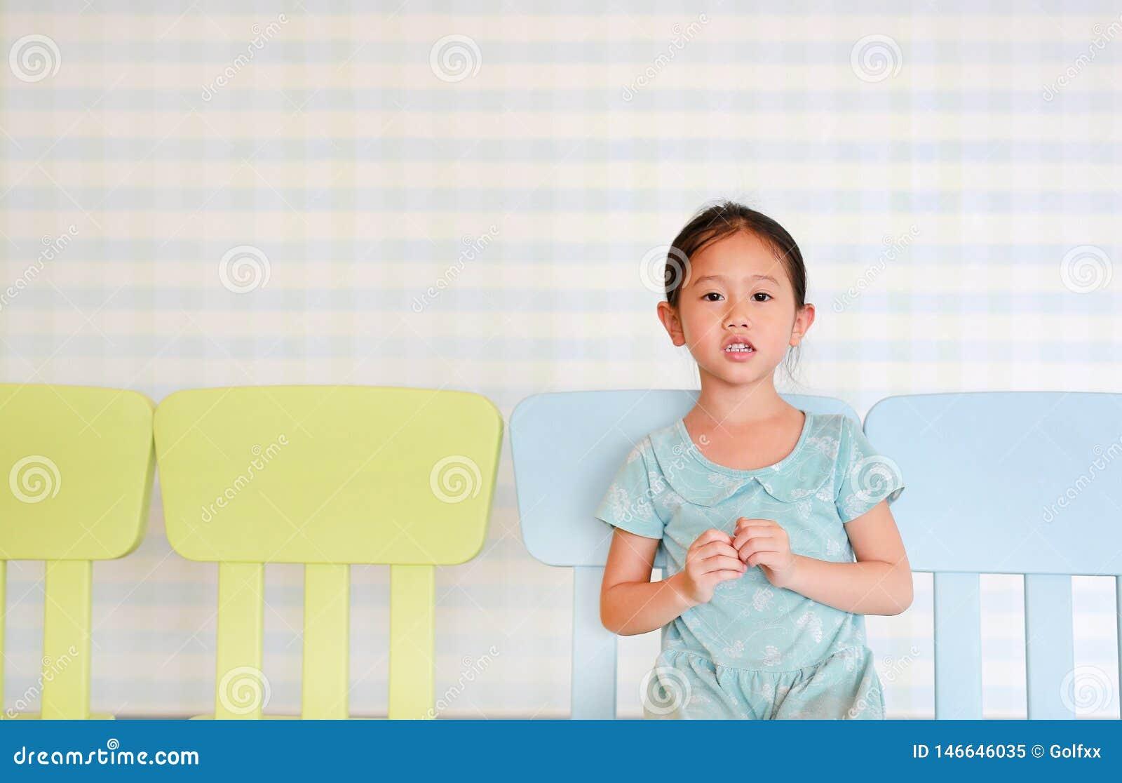 Mała preschool dziewczyna w dziecina izbowym obsiadaniu na plastikowym dziecka krześle patrzeje kamerę