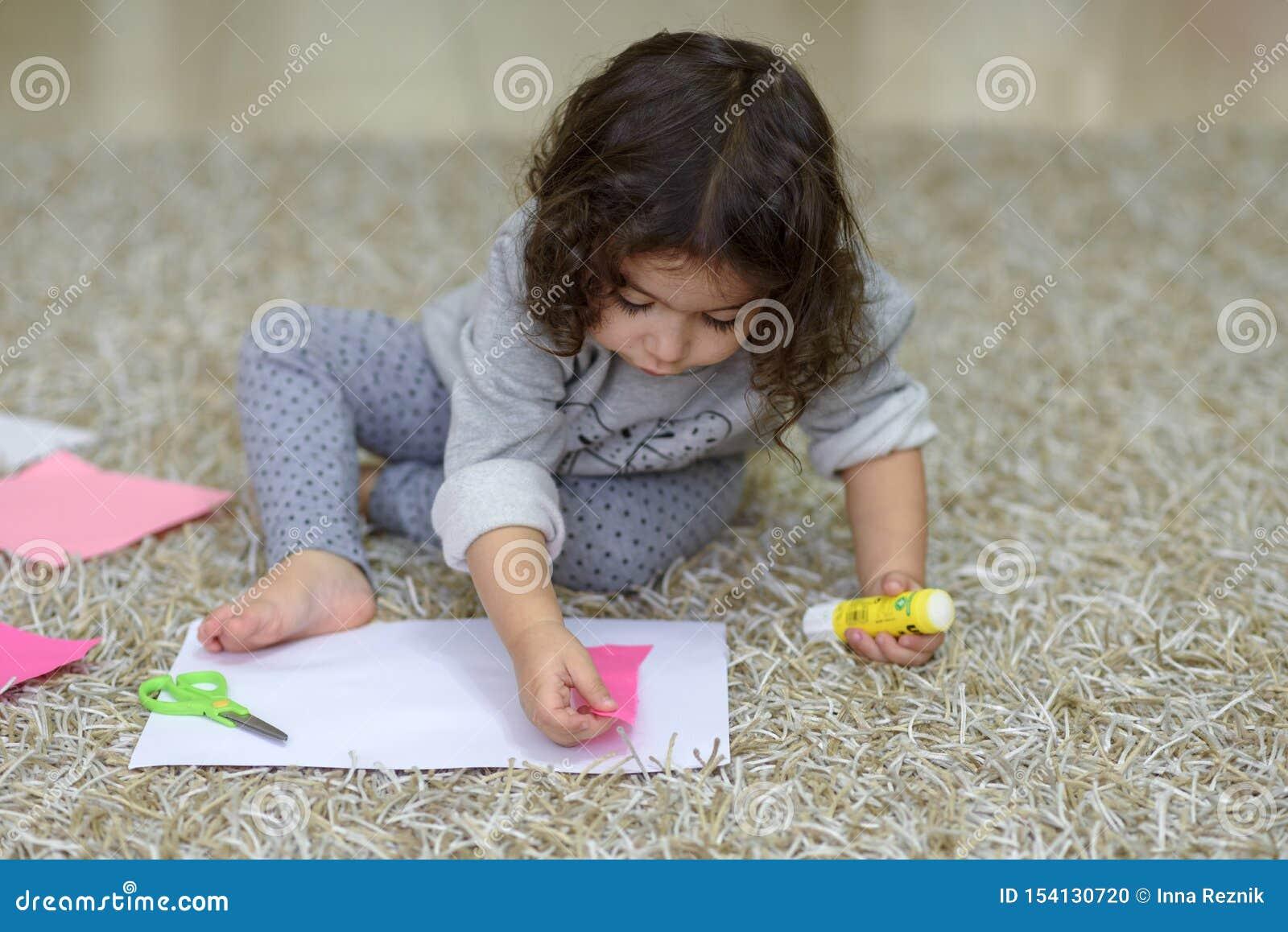 Mała preschooler berbecia dziewczyna klei kolorowego papier