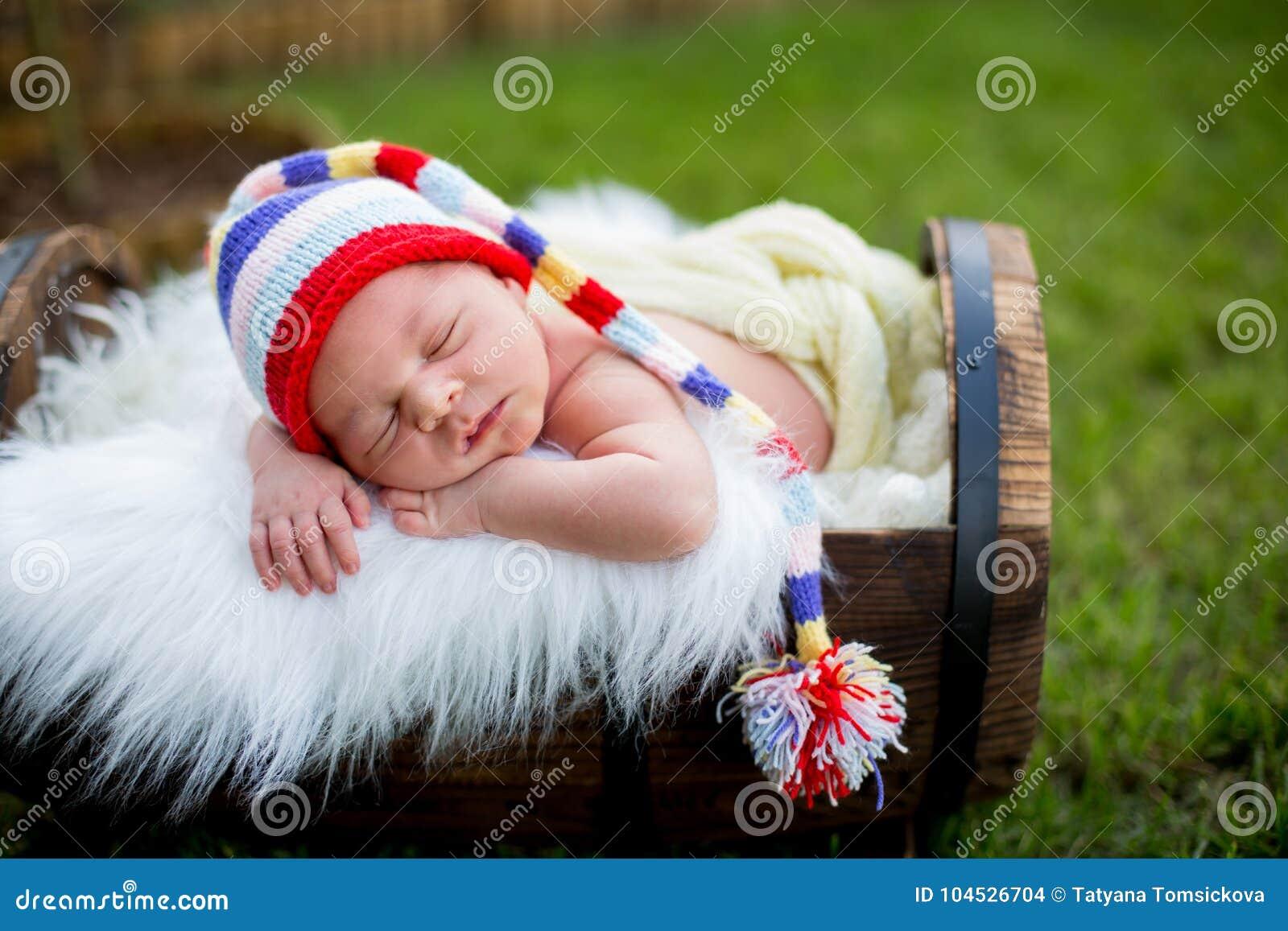 Mała słodka nowonarodzona chłopiec, śpi w skrzynce z trykotowym pa