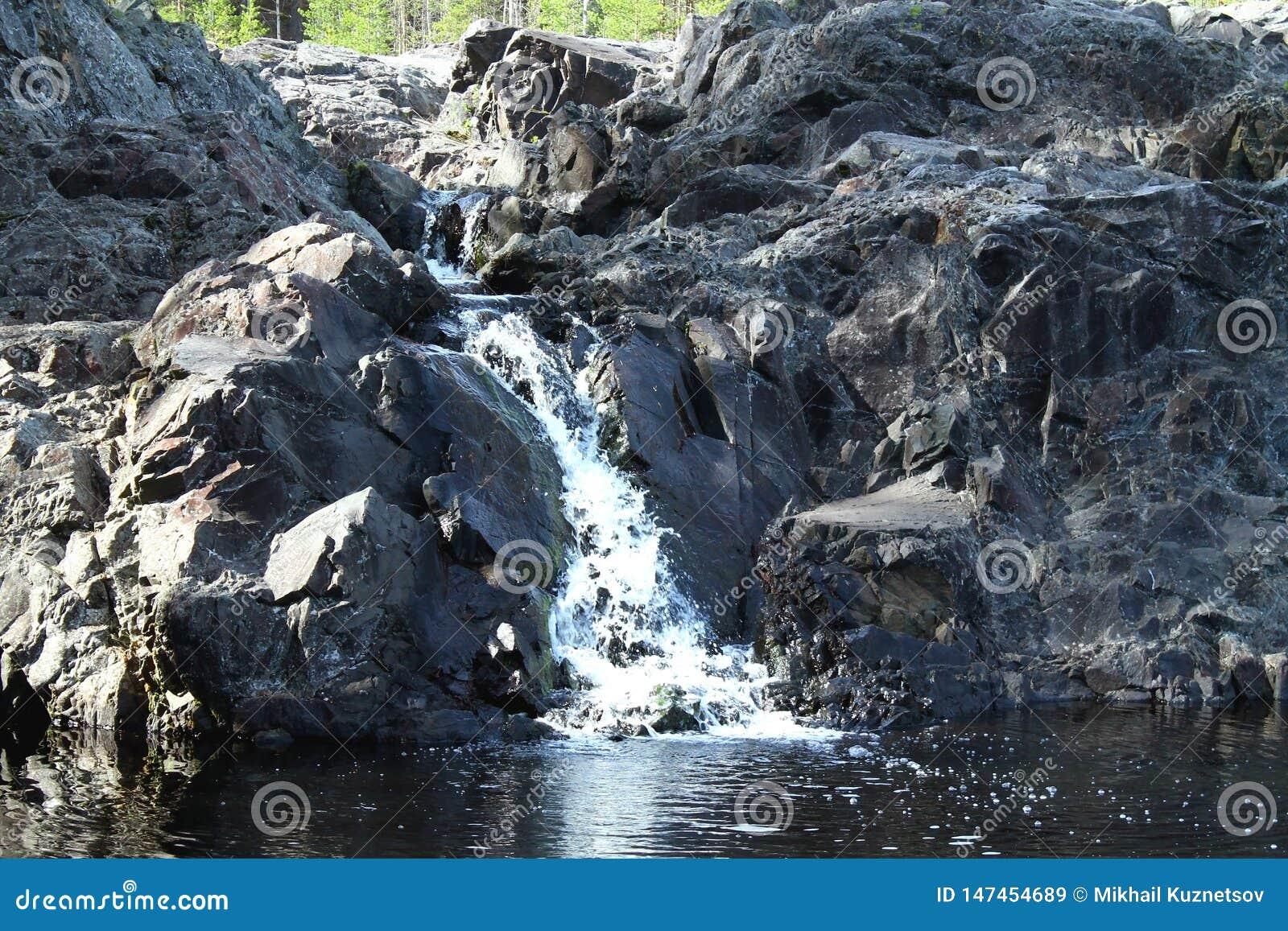 Mała siklawa w Karelia w lesie z skałami