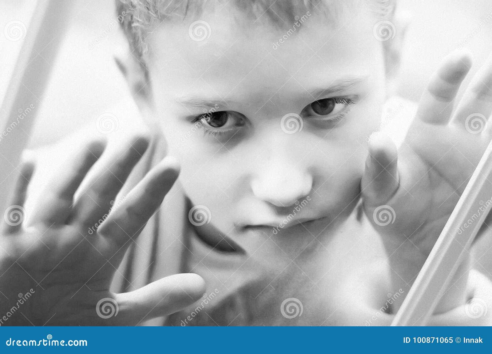 Mała smutna chłopiec patrzeje out okno Czarny i biały fotografia zakończenia dziecko Głodny dziecko je chleb z dużymi jasnymi ocz