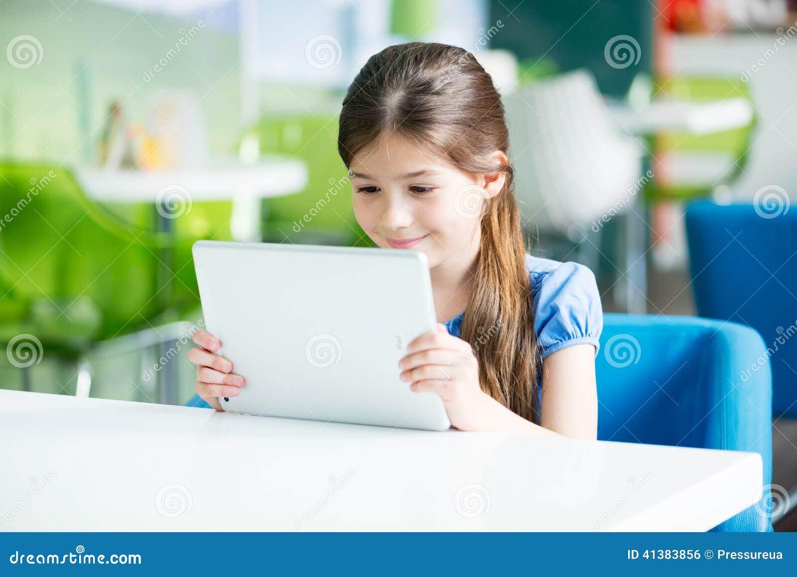 Mała uśmiechnięta dziewczyna z Jabłczanym iPad powietrzem