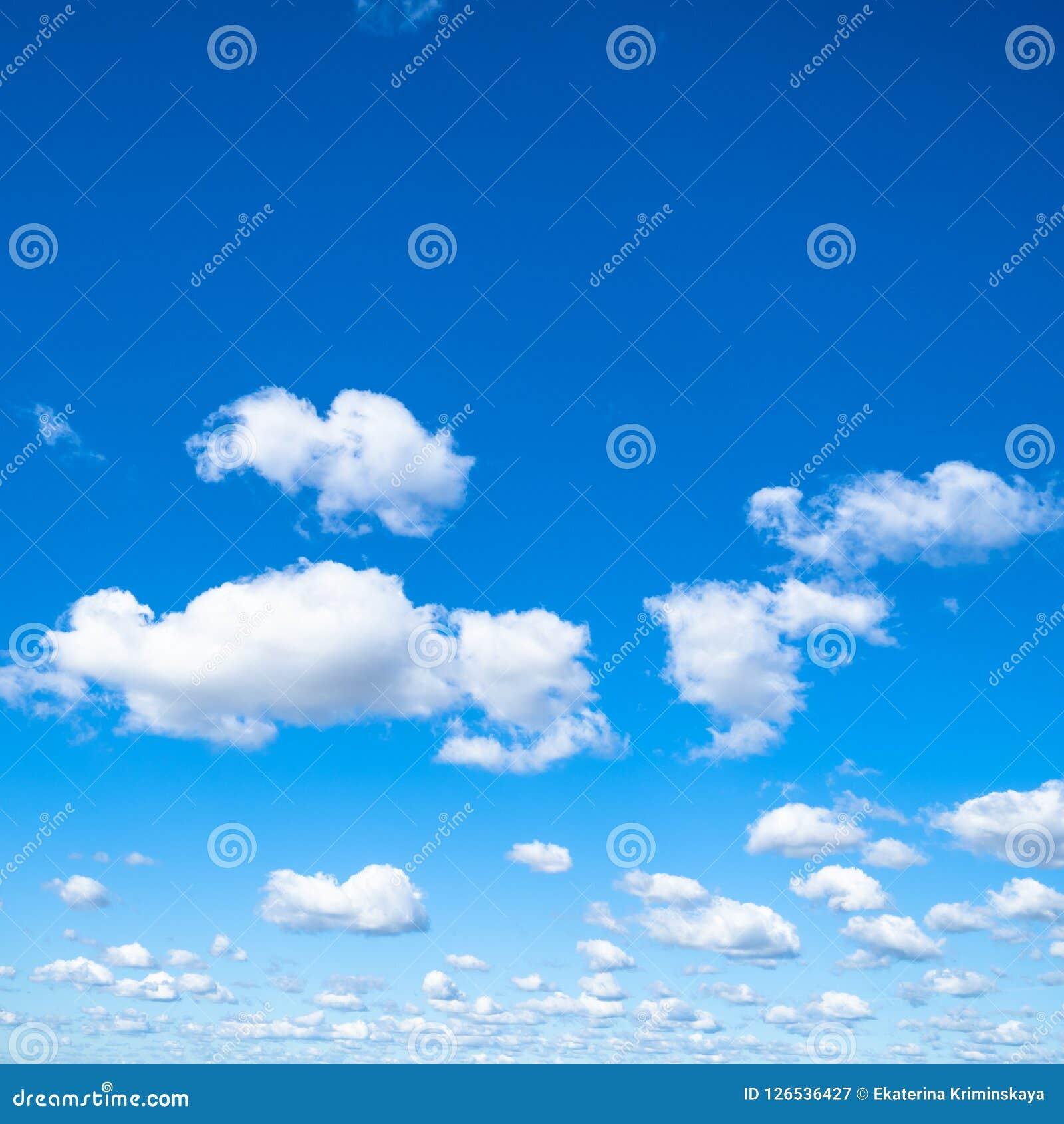 Małe bufiaste chmury w niebieskim niebie w słonecznym dniu
