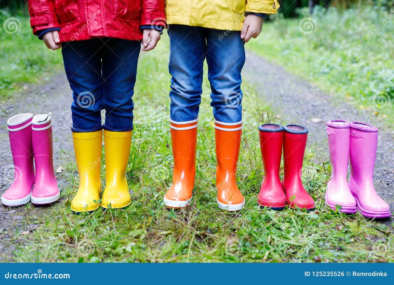 Małe dzieci, chłopiec i dziewczyny w kolorowych podeszczowych butach, Dzieci stoi w jesieni lasowym zakończeniu schoolkids i