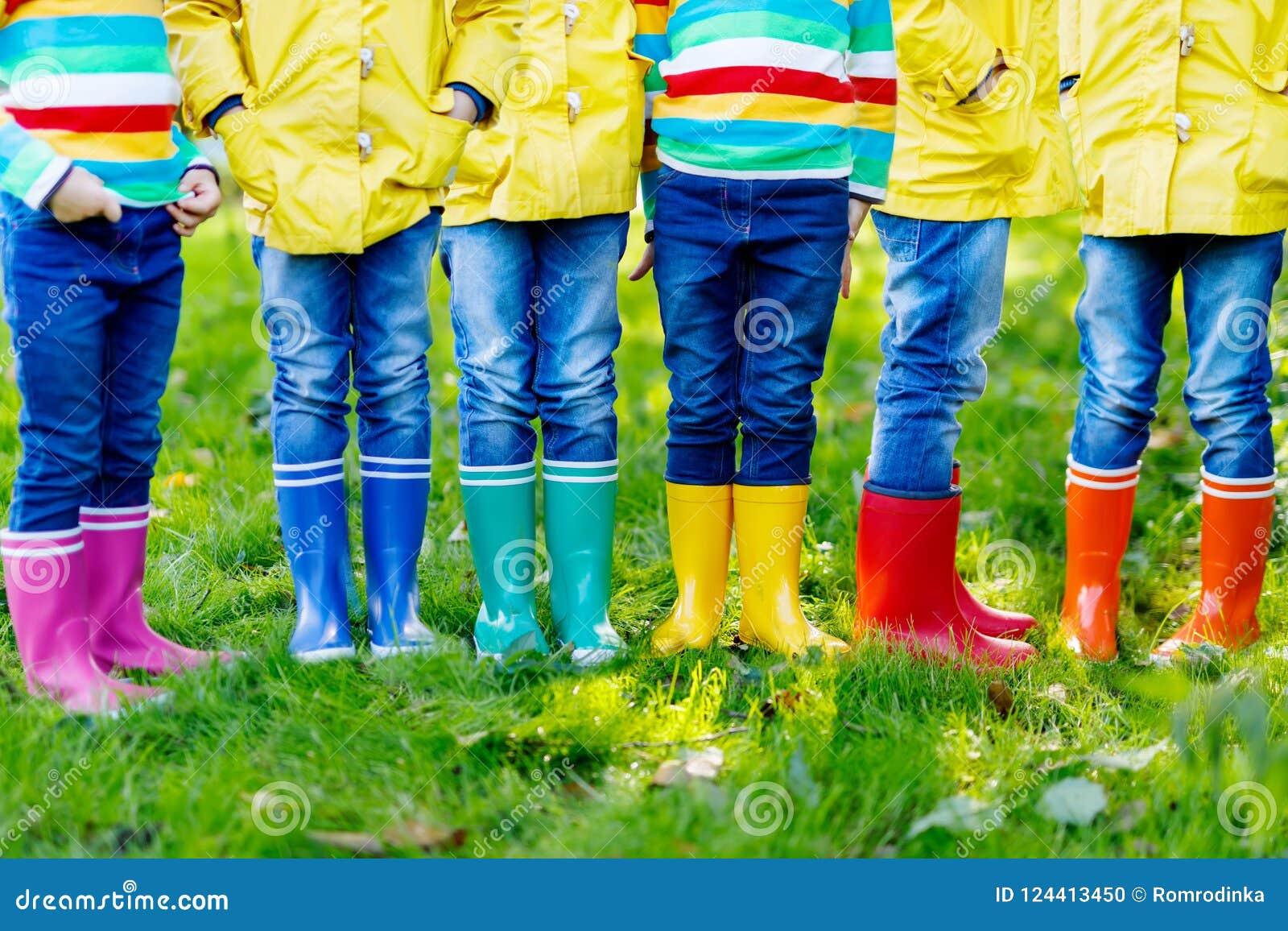Małe dzieci, chłopiec i dziewczyny w kolorowych podeszczowych butach, Zakończenie dzieci w różnych gumowych butach, cajgach i kur