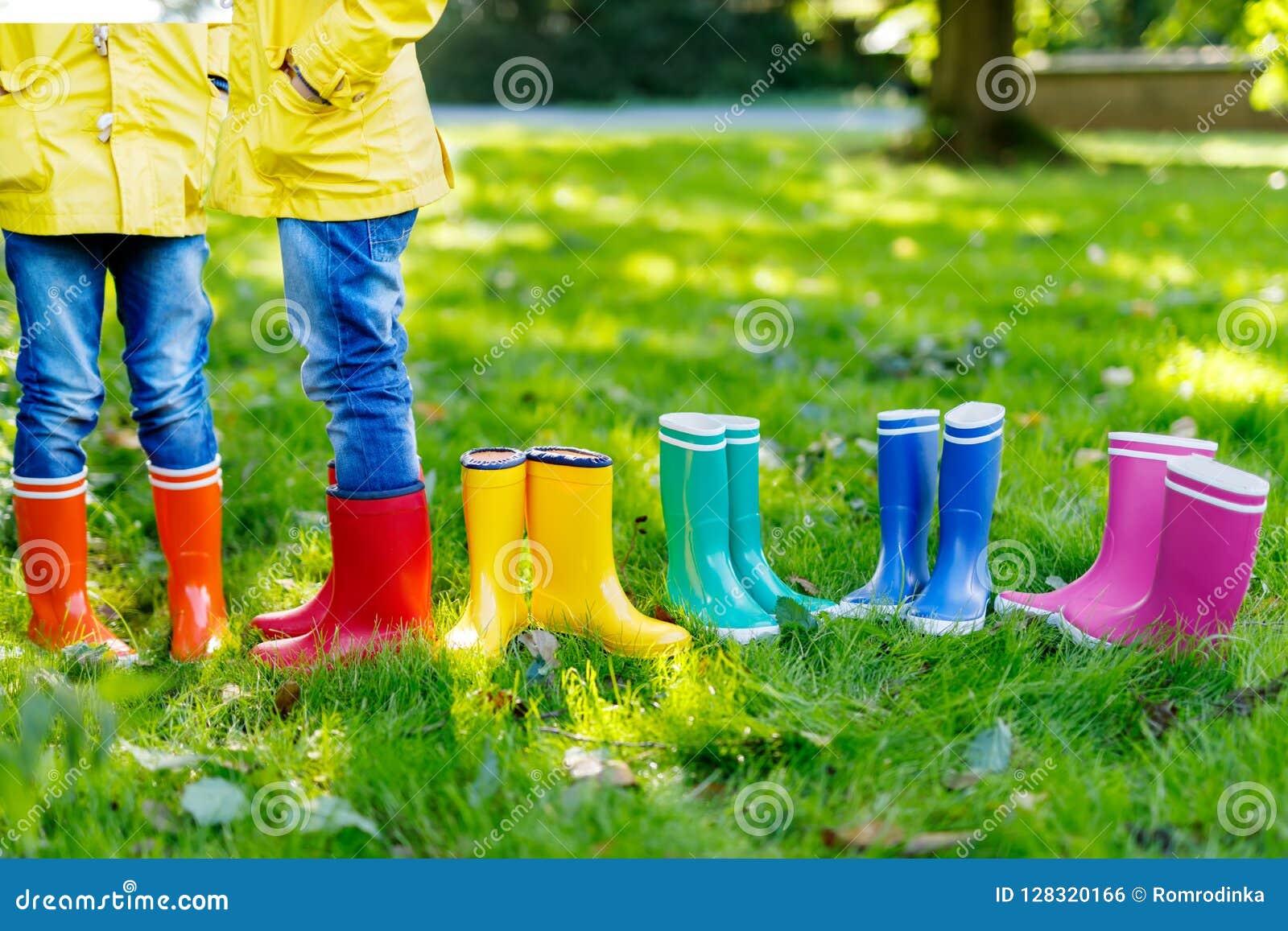 Małe dzieci, chłopiec lub dziewczyny w, cajgach i żółtej kurtce w kolorowych podeszczowych butach