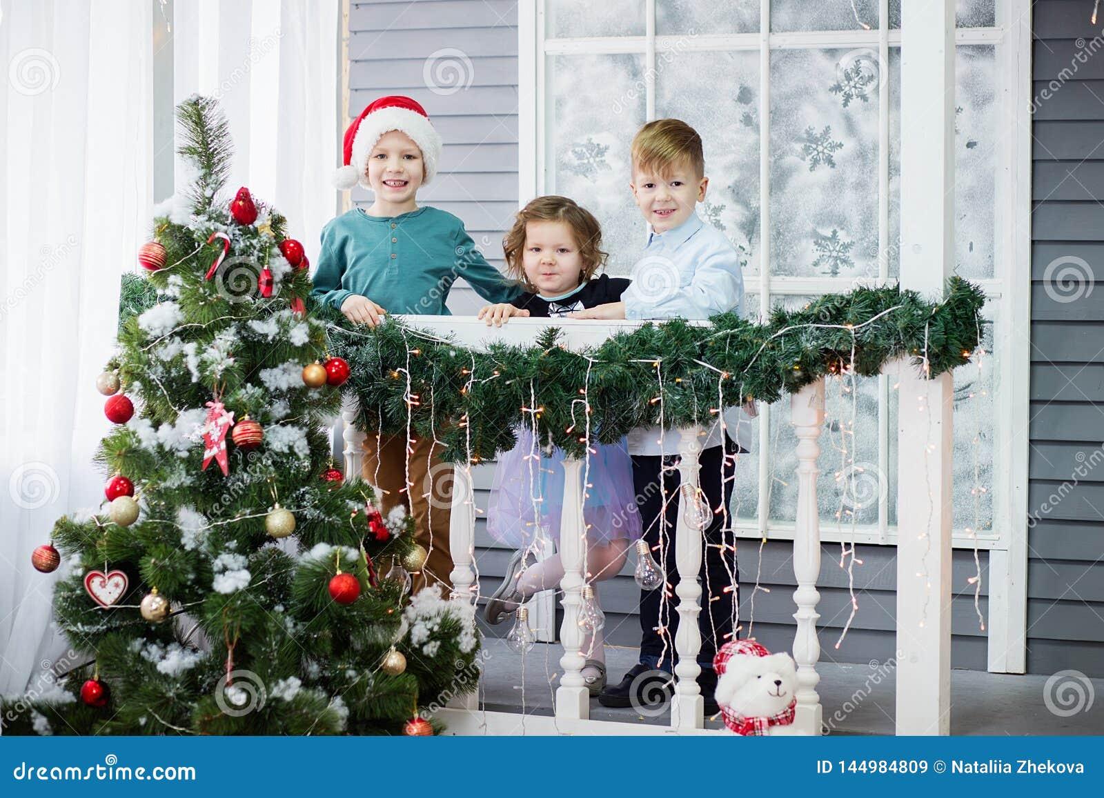 Małe dzieci W oczekiwaniu na nowego rok i boże narodzenia Trzy małego dziecka mają zabawę i bawić się blisko choinki