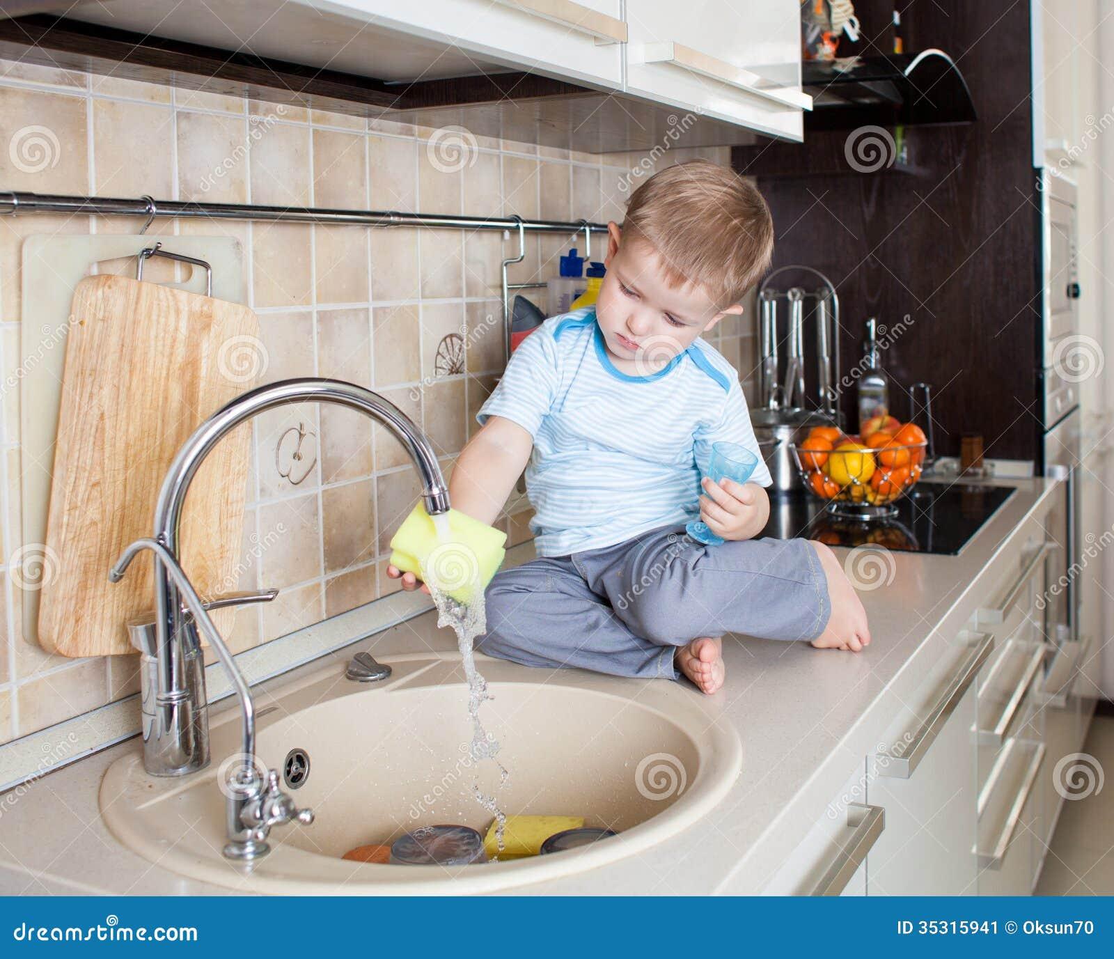 Małe dziecko chłopiec domycia naczynie na kuchni