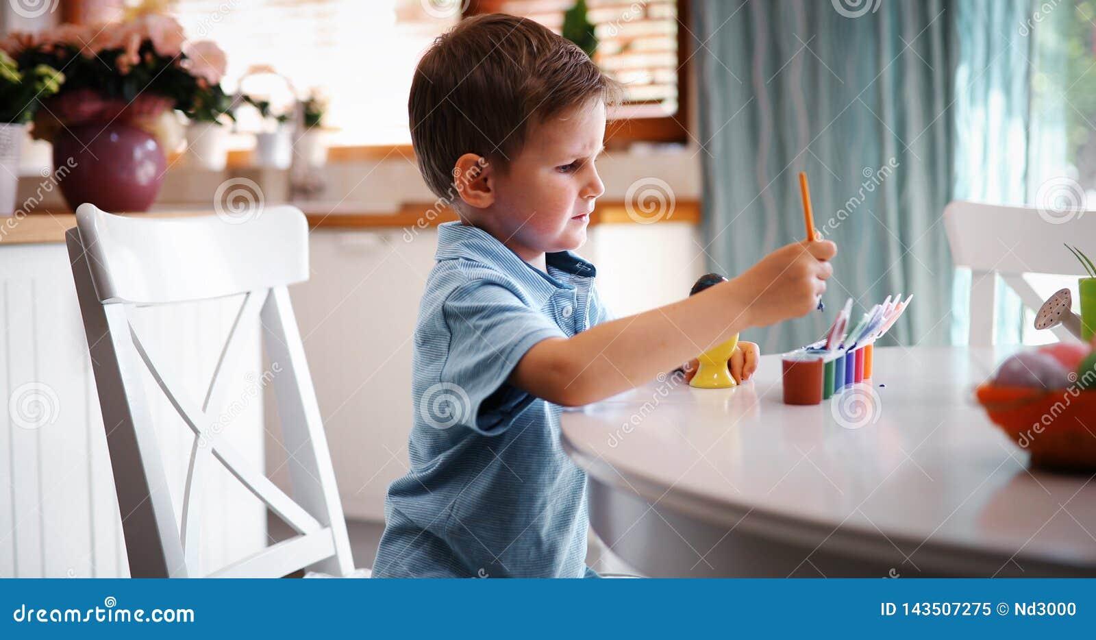Małe dziecko chłopiec kolorystyki jajka dla Wielkanocnego wakacje w domowej kuchni