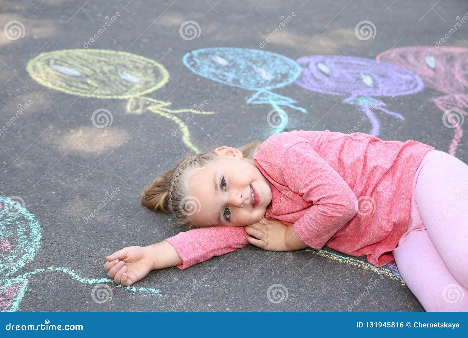 Małe dziecko kłama blisko kredowego rysunku balony