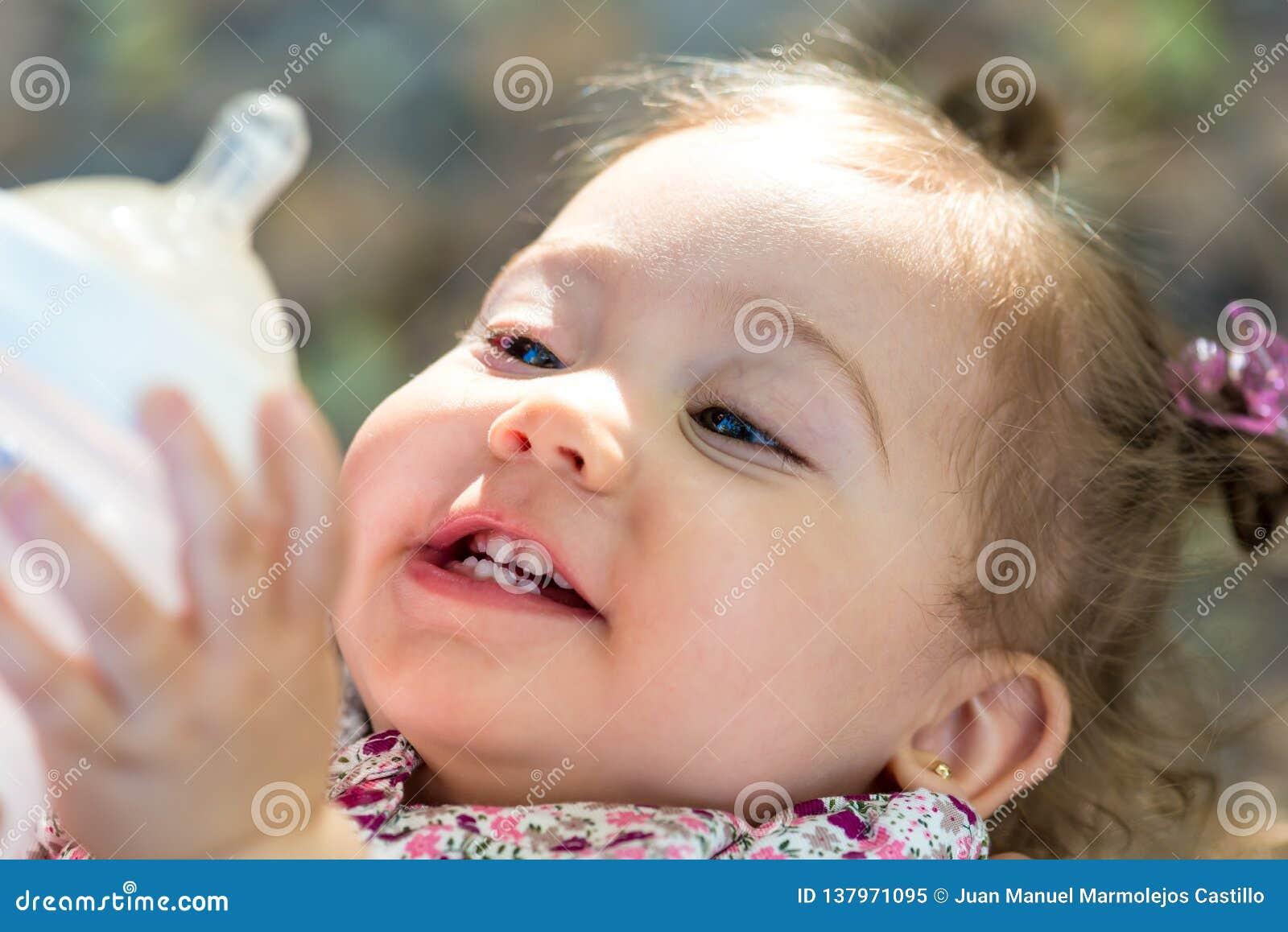 Małe dziecko pije mleko od dziecko butelki outdoors