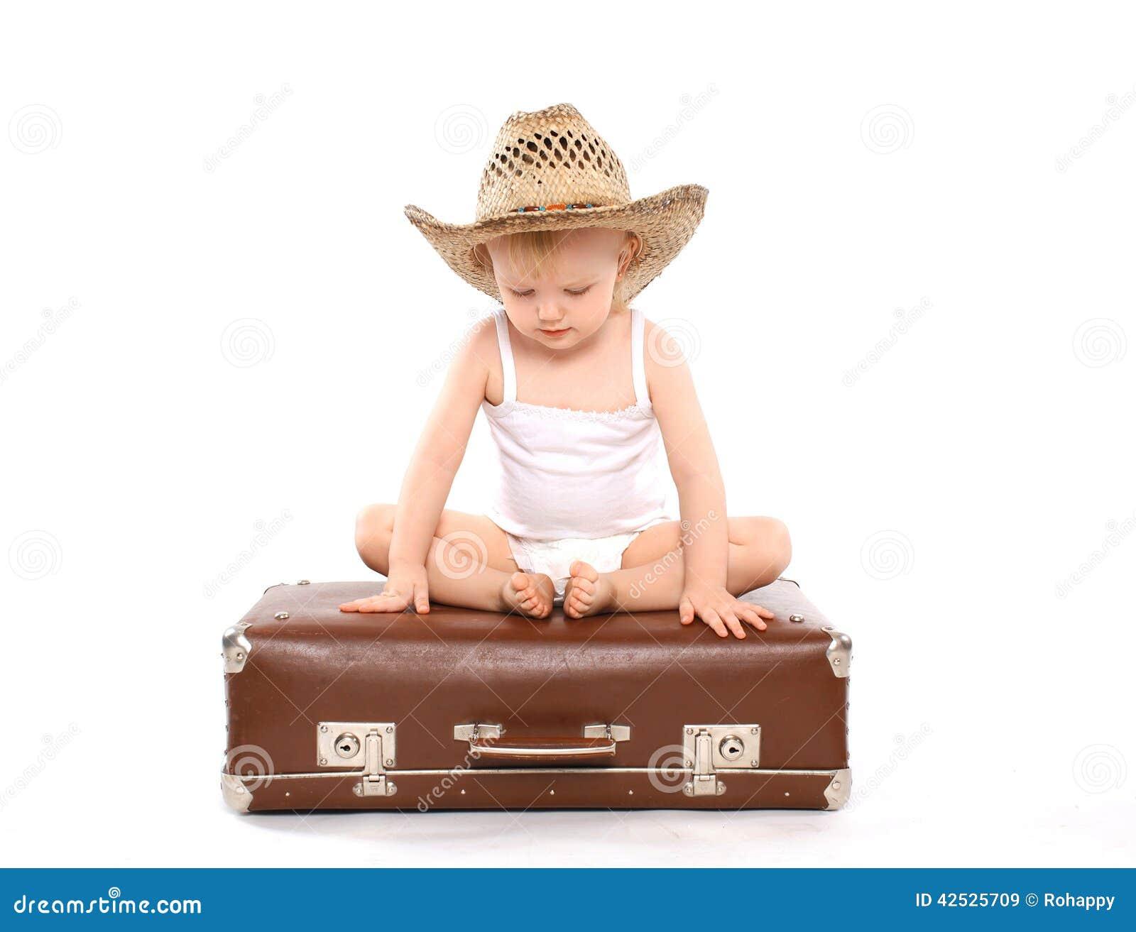 Małe dziecko w słomianego lata kapeluszowym obsiadaniu na walizce