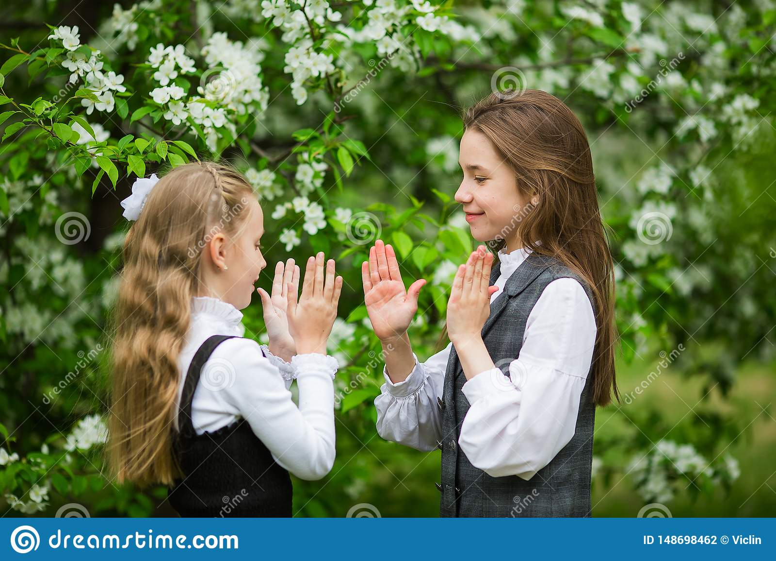 Małe dziewczynki w eleganckich mundurkach szkolnych bawić się outdoors w kwitnie jabłko parku