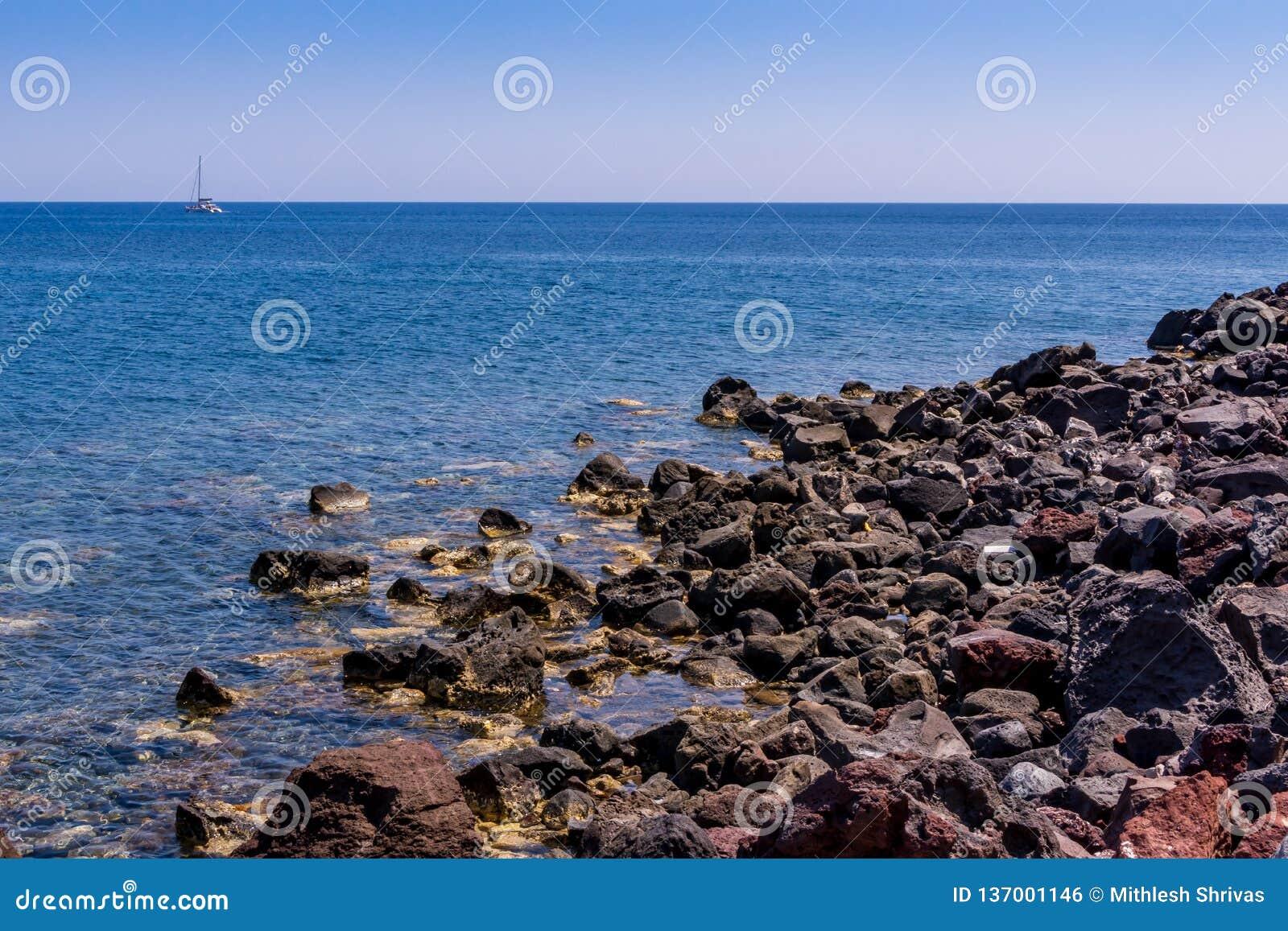 Małe skały, morze i yatch, santorini wyspa, Greece