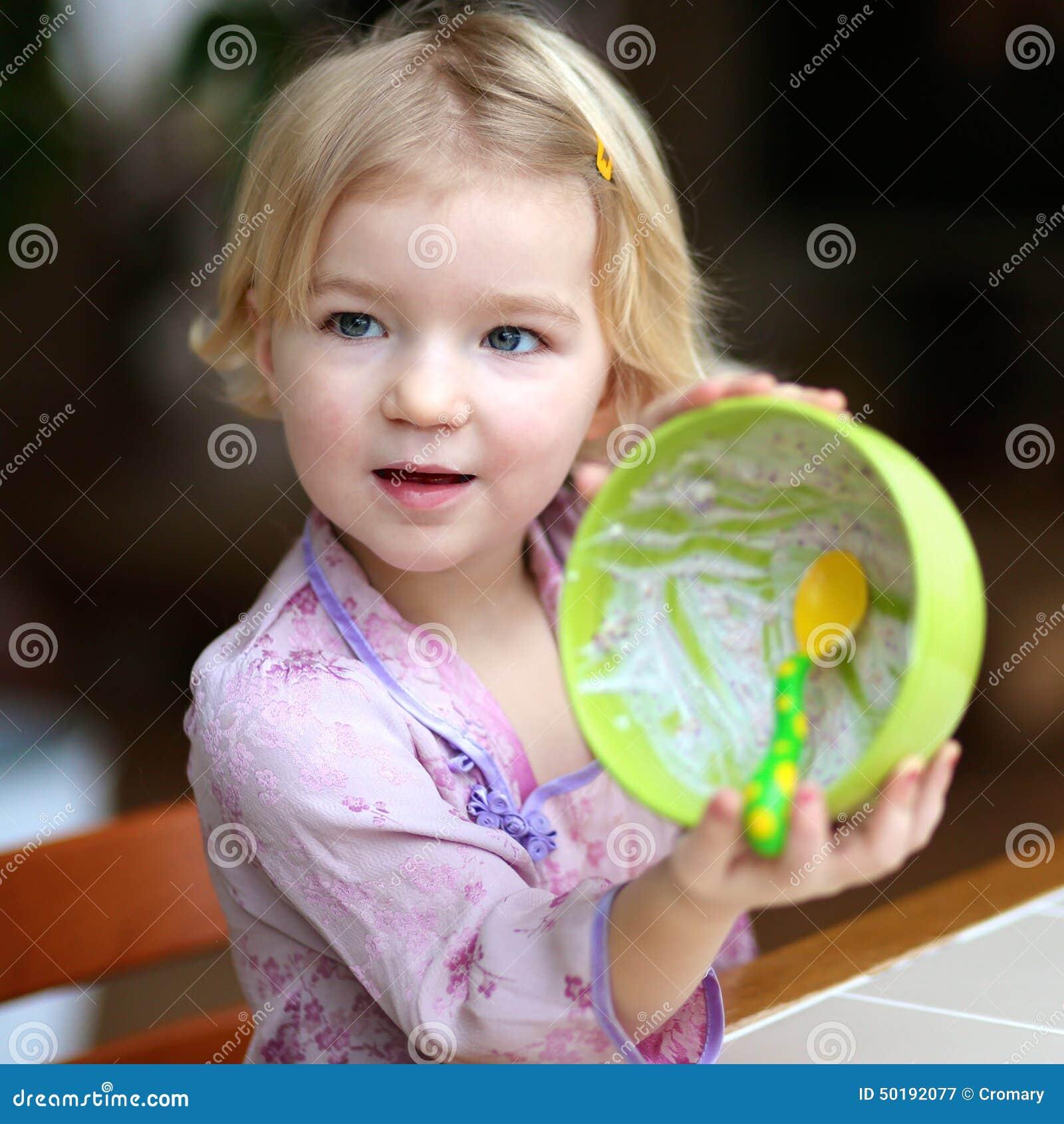 Małej dziewczynki łasowania muesli z jogurtem dla śniadania