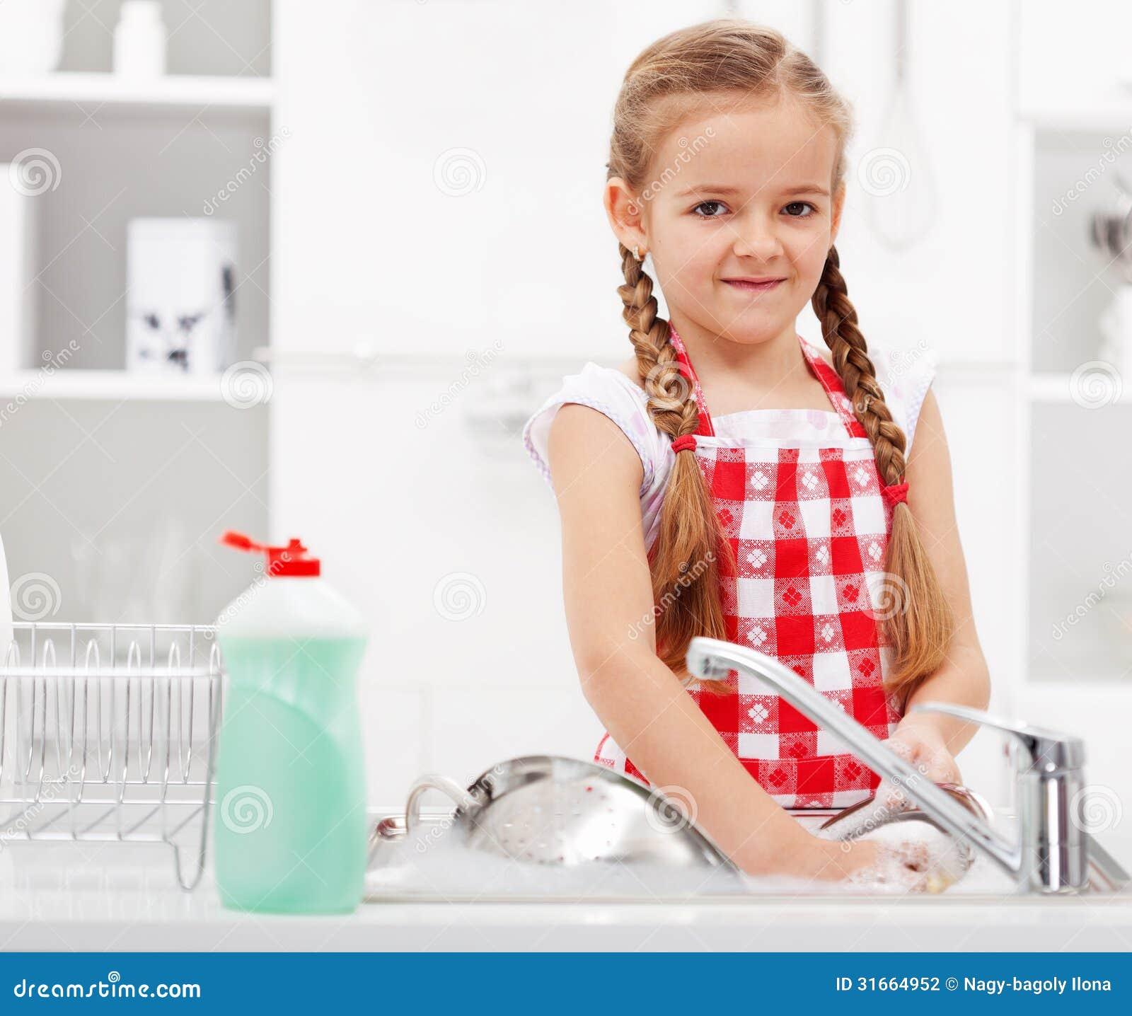 Małej dziewczynki domycia naczynia w kuchni