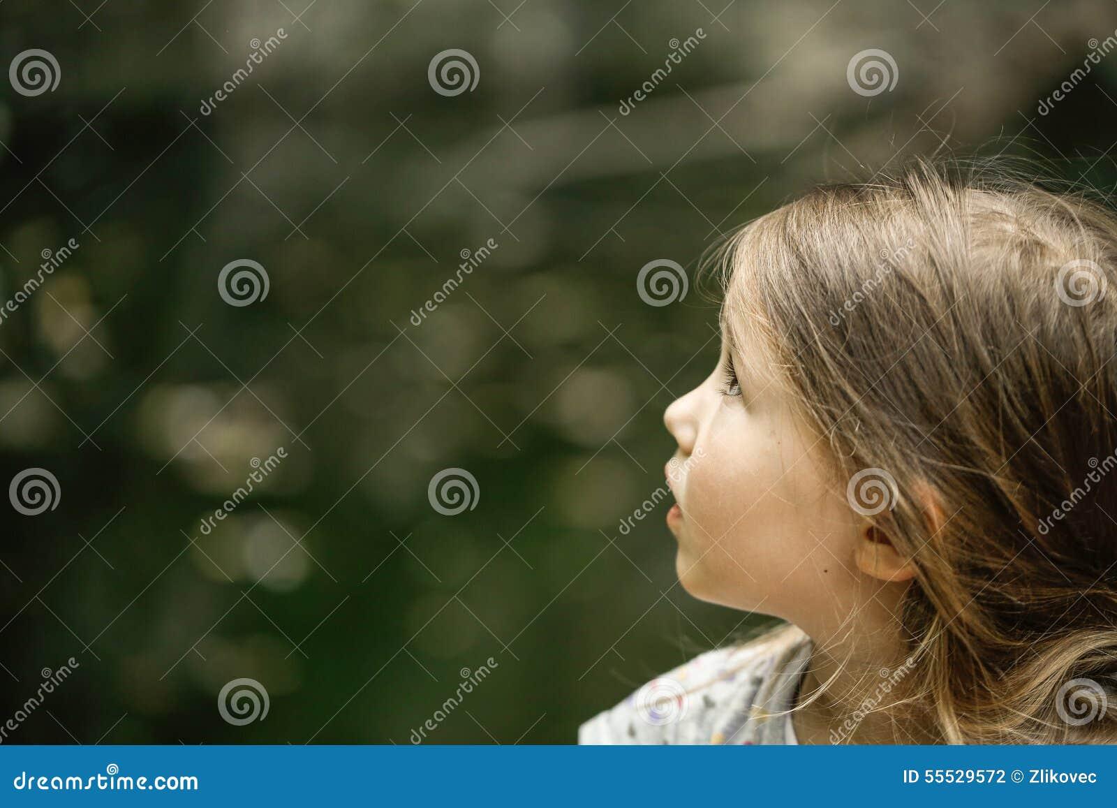 Małej dziewczynki dopatrywania drzewa, nieba i ptaki w respekcie,