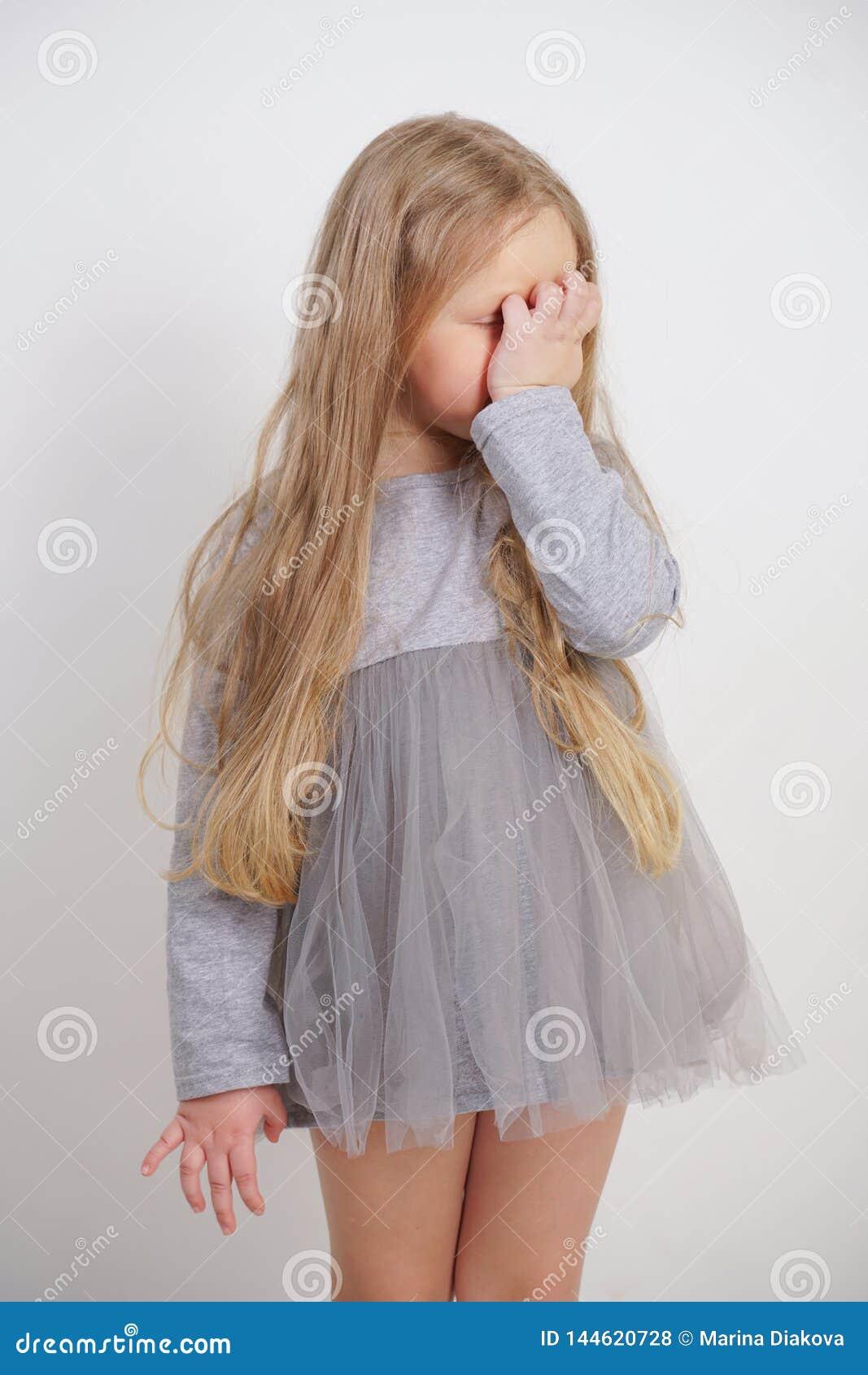Małej dziewczynki dziecka pozycja z ręką w twarzy z facepalm symbolem na białym tle w studiu