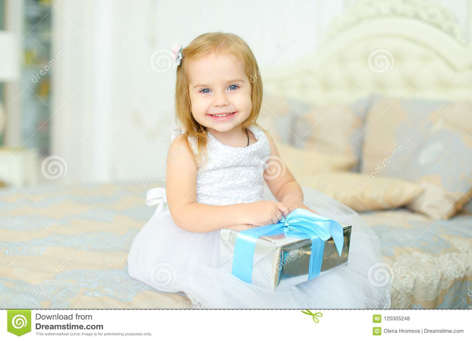 Małej dziewczynki obsiadanie na łóżku z teraźniejszą i jest ubranym biel suknią