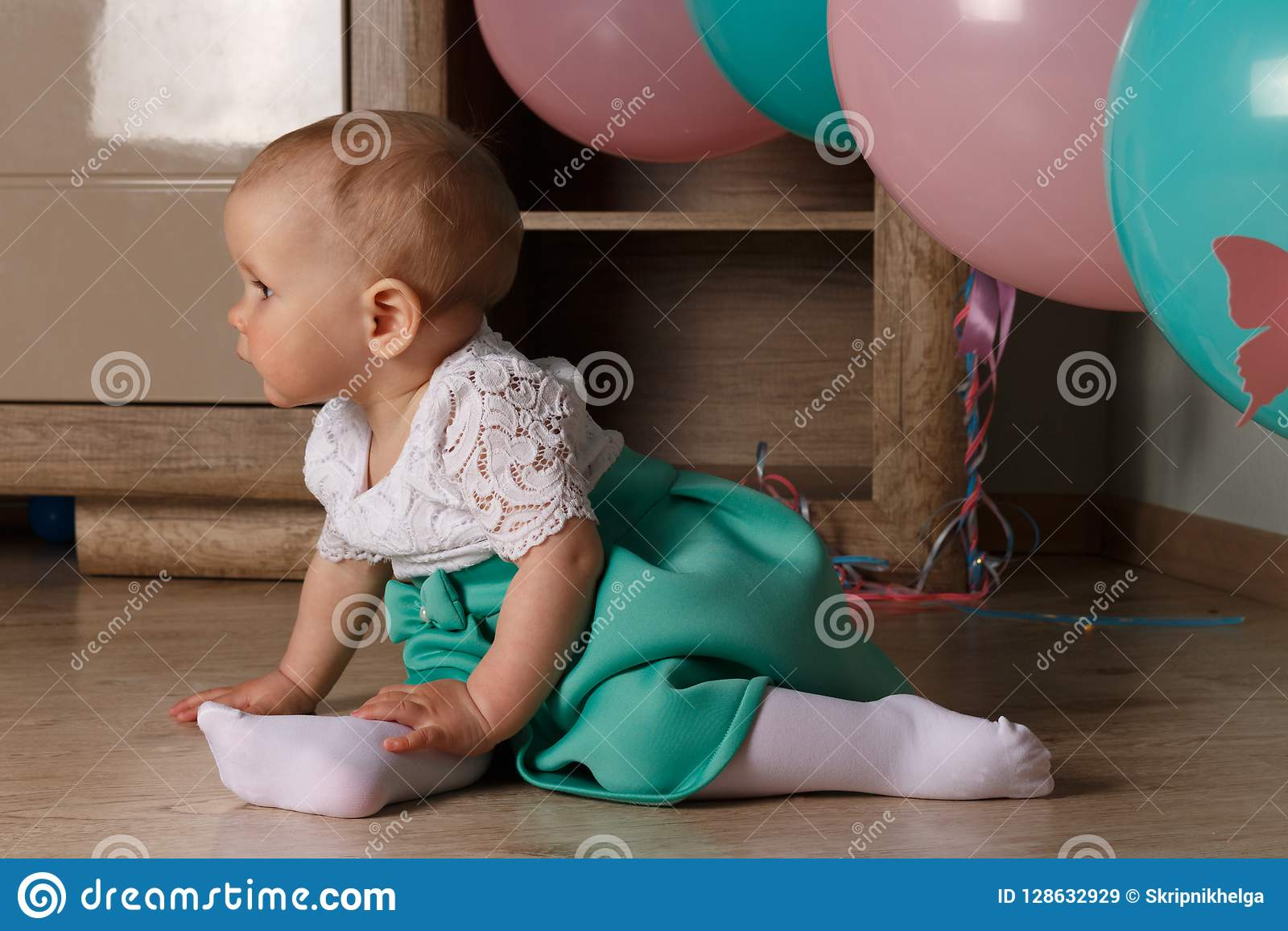 Małej dziewczynki obsiadanie na podłoga w pokoju obok balonów, pierwszy urodziny, świętuje jeden roczniaka błękitny i różowy piłk