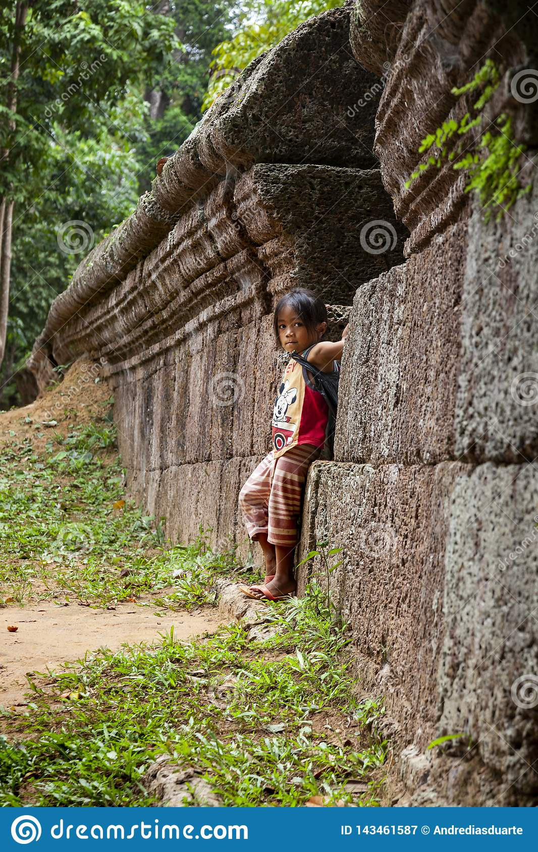 Małej dziewczynki pozycja przeciw starej kamiennej ścianie