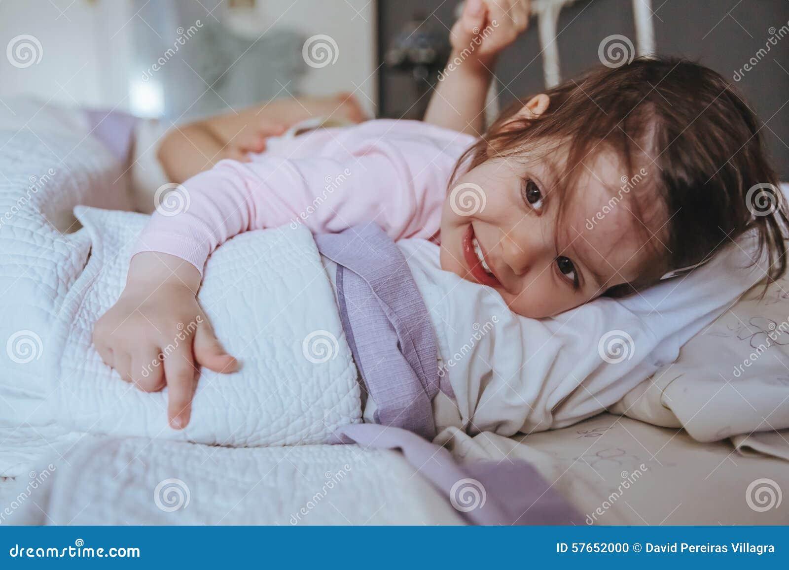 Małej dziewczynki uśmiechnięty lying on the beach nad łóżkiem