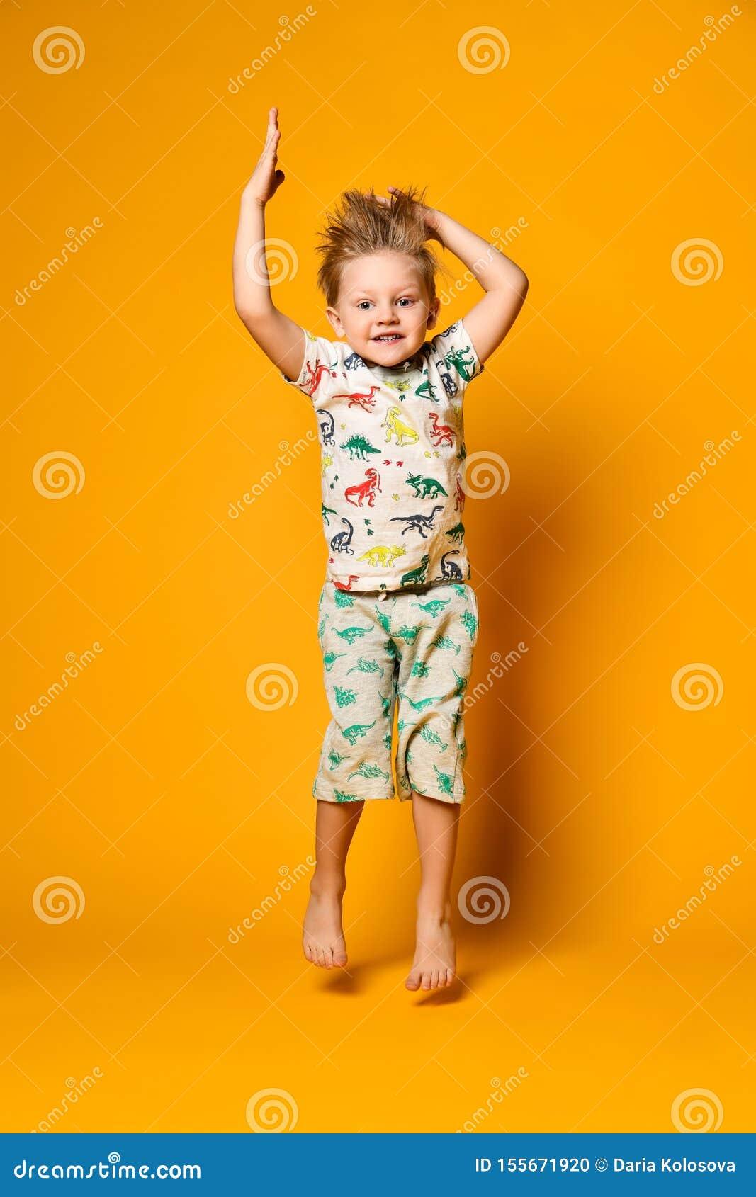Mały śliczny blond chłopiec preschooler w piżamach z dinosaurami ma zabawę radość w studiu nad żółtym tłem