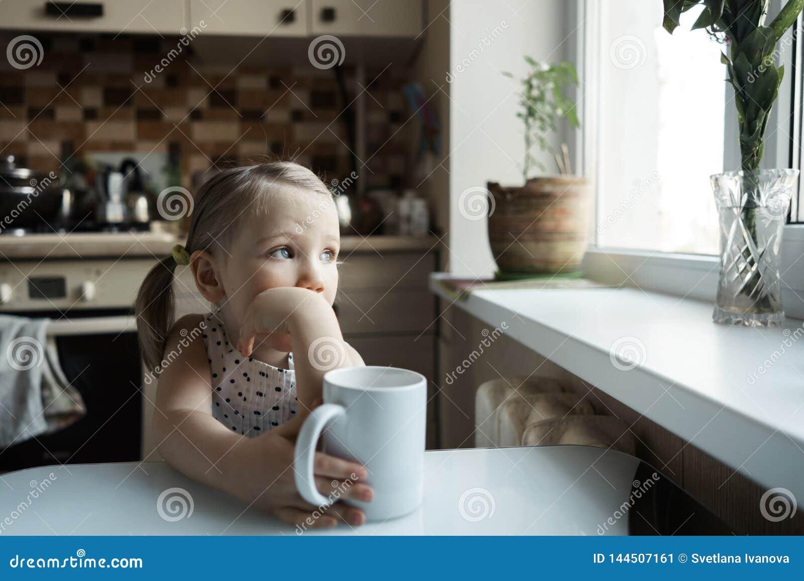 Mały śliczny dziewczyny obsiadanie przy stołem w kuchni