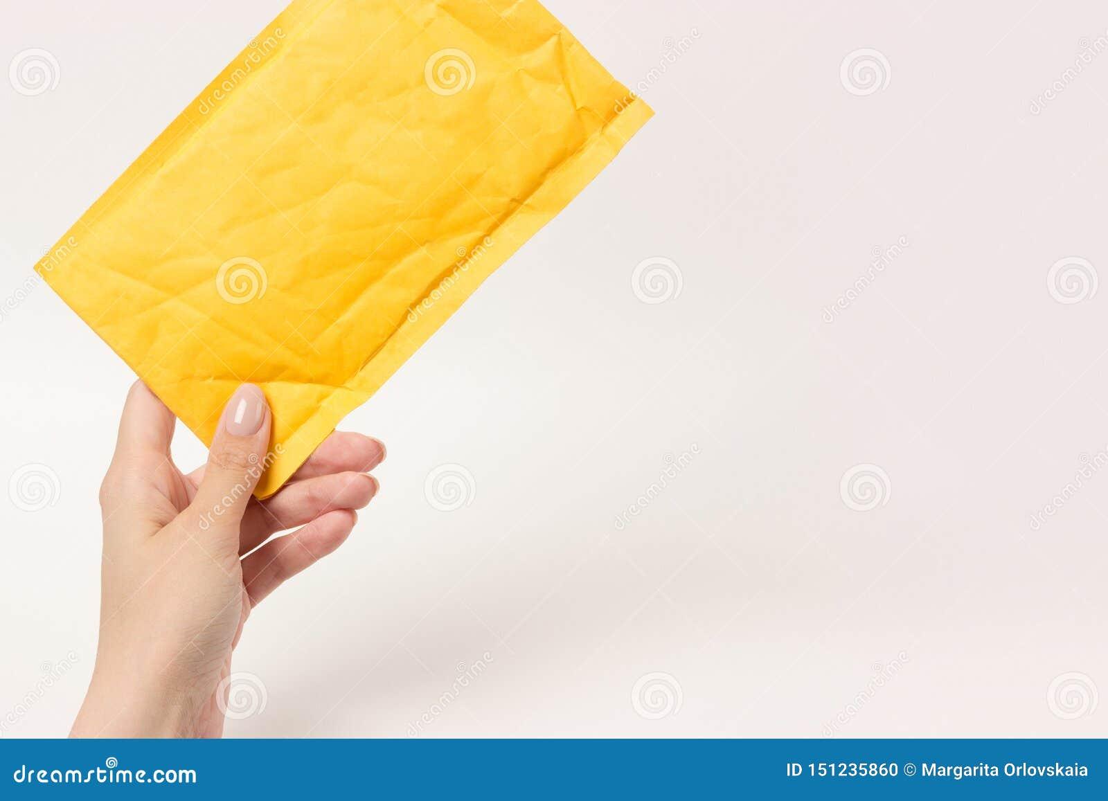 Mały żółty pocztowy pakuneczka om bielu tło