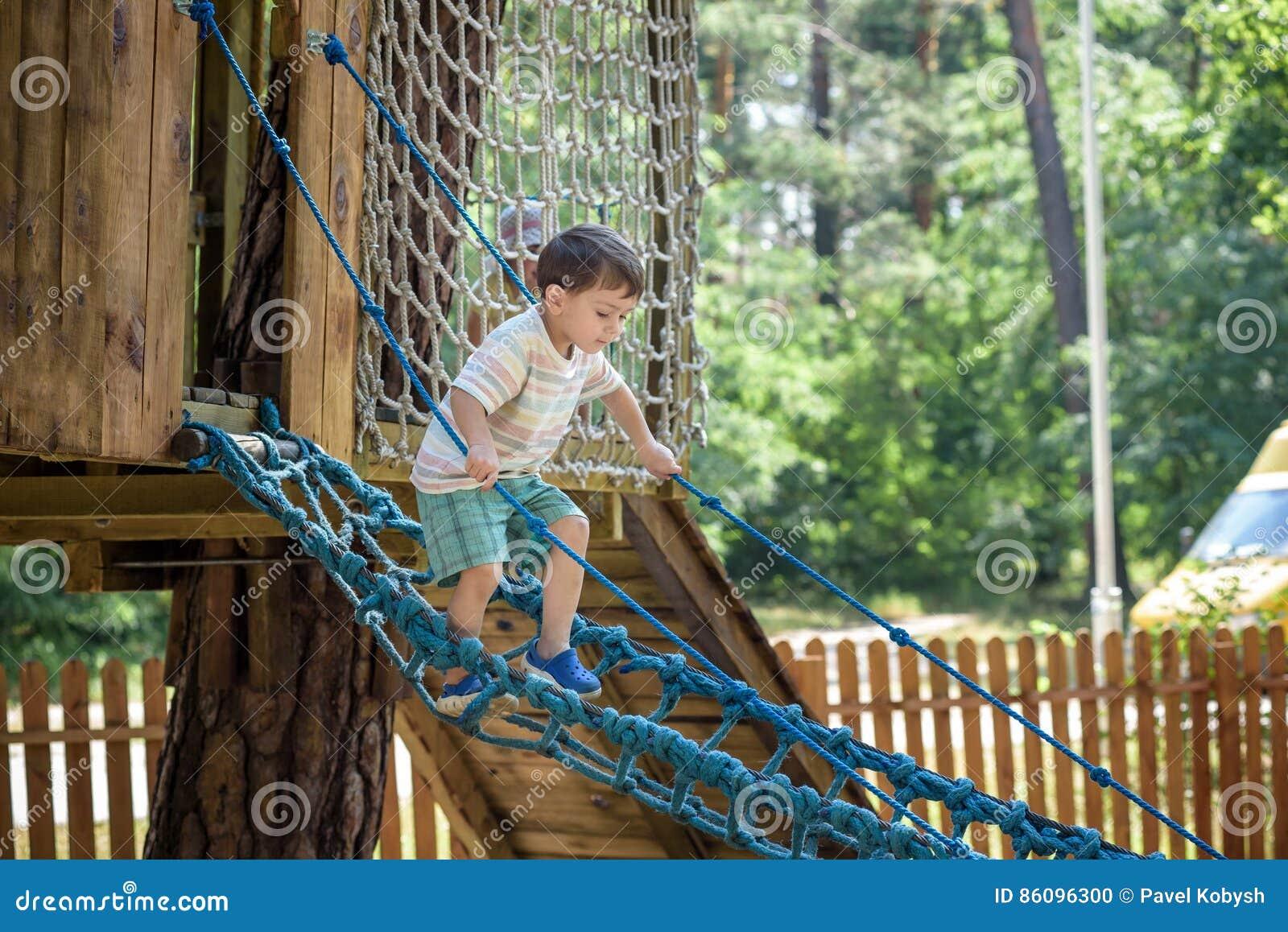 Mały arywista bierze linowego most Chłopiec zabawa czas, dzieciaka pięcie na pogodnym ciepłym letnim dniu