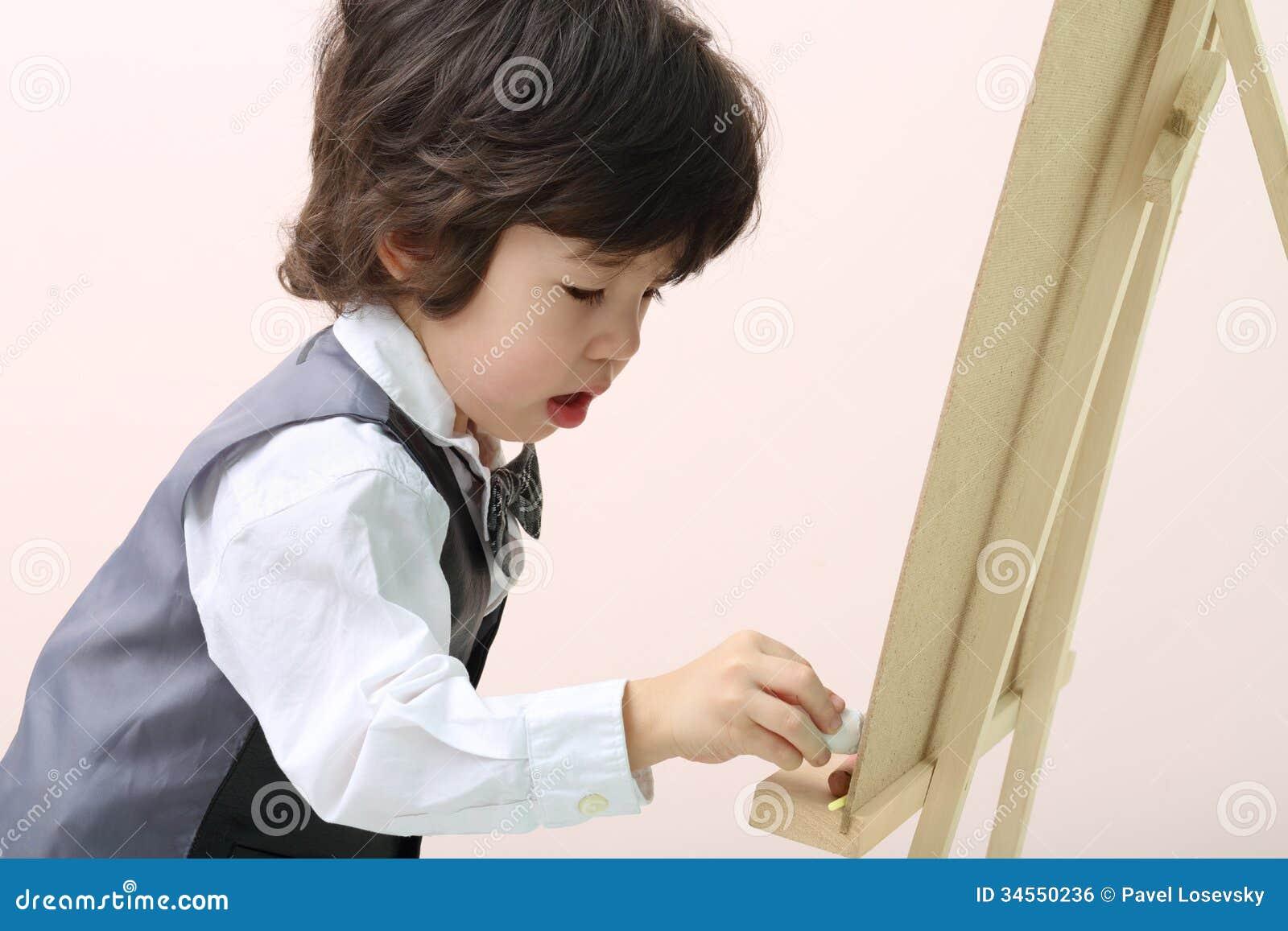 Mały brunet koncentrująca chłopiec rysuje kredą przy chalkboard