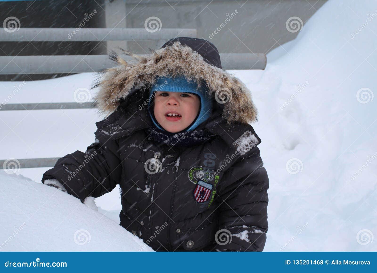 Mały chłopiec odprowadzenie w zimie w śniegu w jardzie