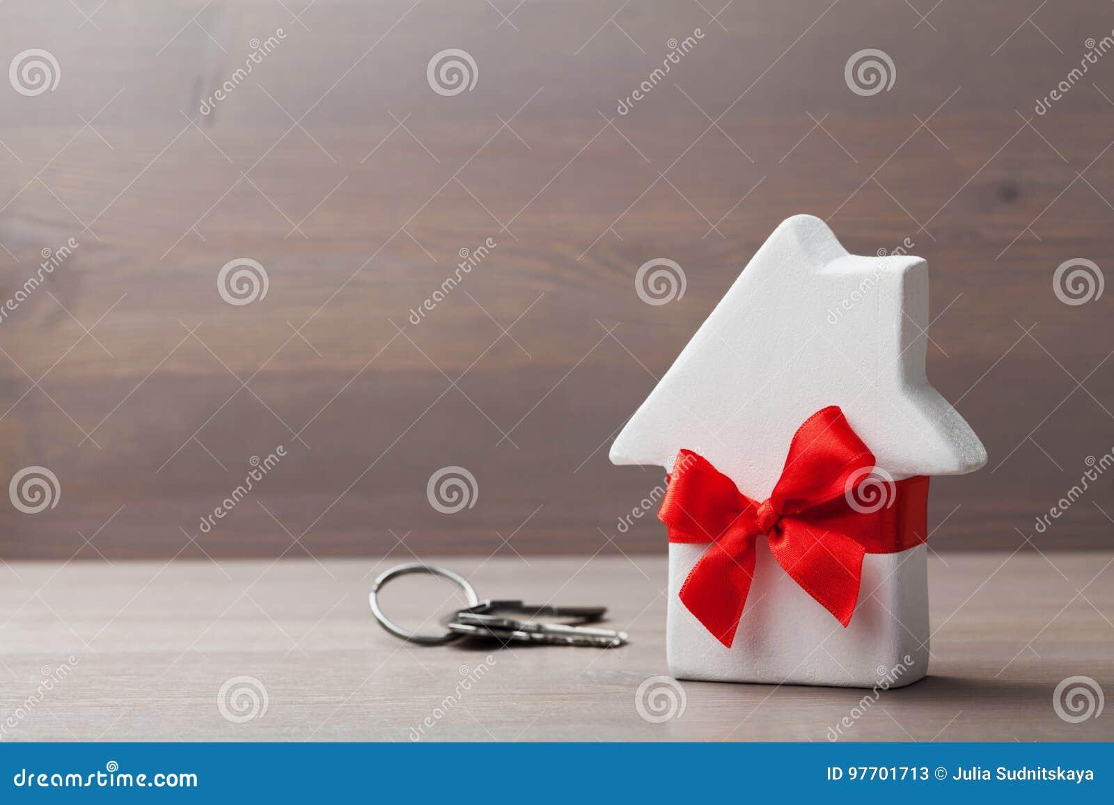 Mały dom dekorujący bielu łęku czerwony faborek z wiązką klucze na drewnianym tle Prezent, nieruchomość lub kupować nowego dom,