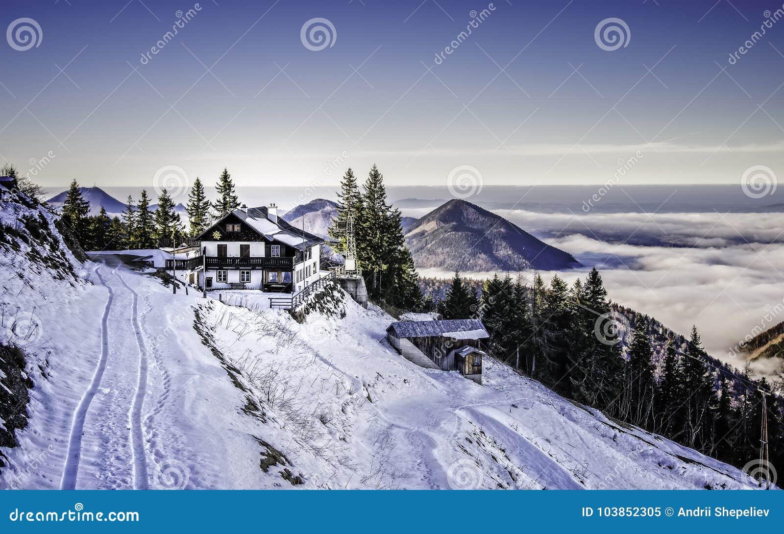Mały dom na śnieżnym zboczu góry obok wąskiej drogi