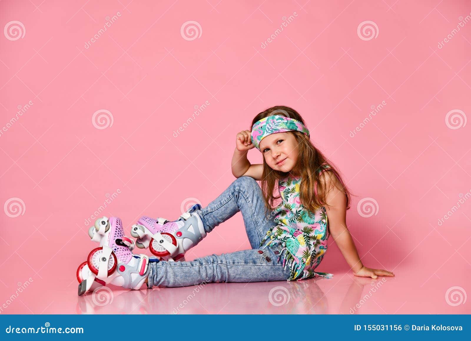Mały dziecko blondynu dziecka obsiadanie z rolkowymi łyżwami w białej koszula hairband szczęśliwym uśmiechu na różowym pracownian
