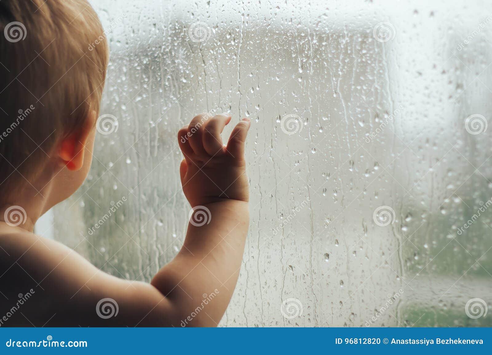 Mały dziecko patrzeje okno z podeszczową ręką tylko