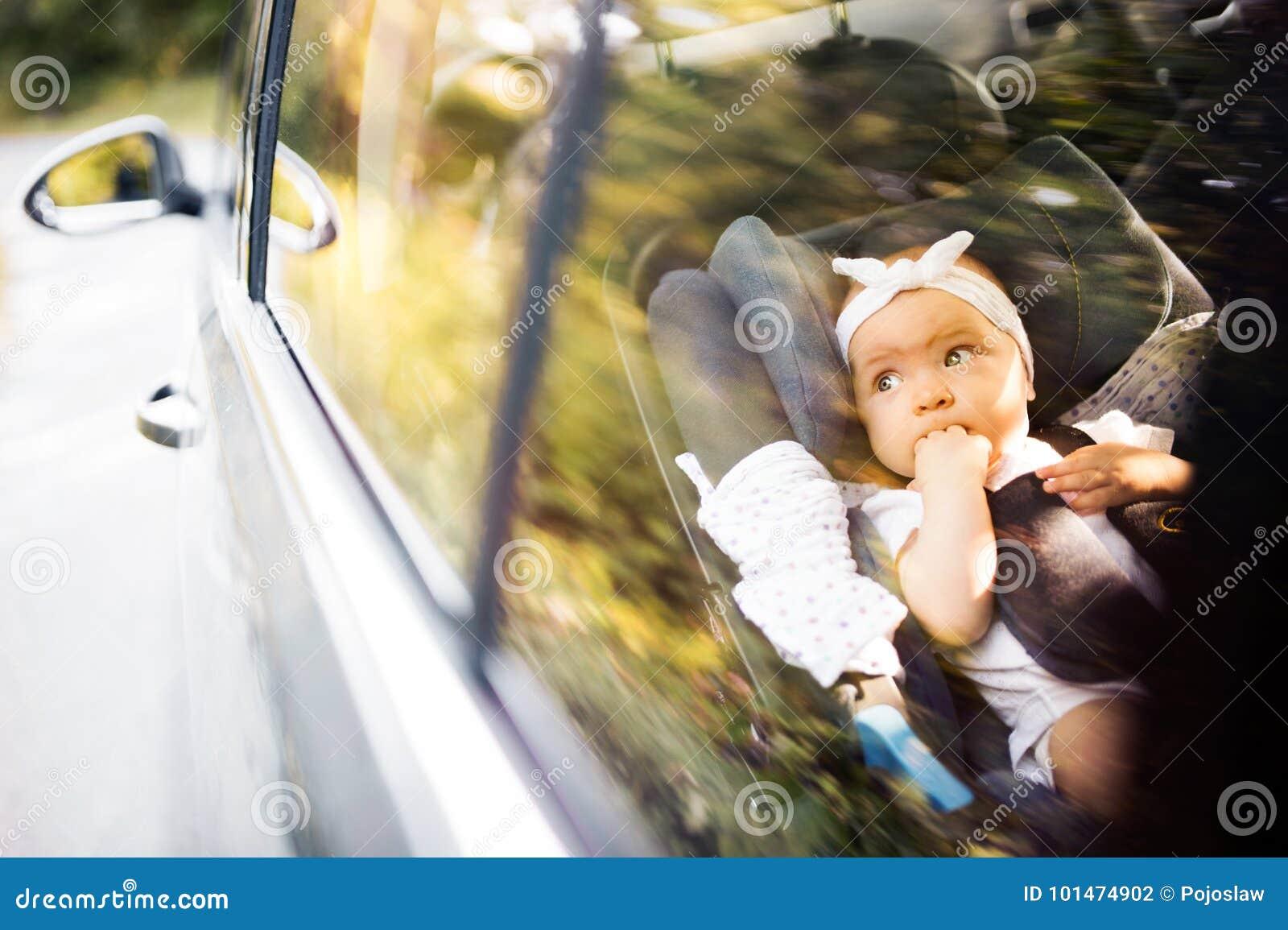 Mały dziecko przymocowywał z ochrona paskiem w zbawczym samochodowym siedzeniu